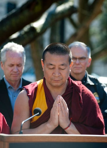 Geshe Gedun, a Tibetan Buddhist member of the Drepung Gomang Center for Engaging Compassion in St. Matthews, chant a closing prayer at the vigil chants a closing prayer at the end of the vigil. Behind him are Louisville Metro Mayor Greg Fischer, left, and Louisville Metro Police Chief Steve Conrad, right. 16 March 2019