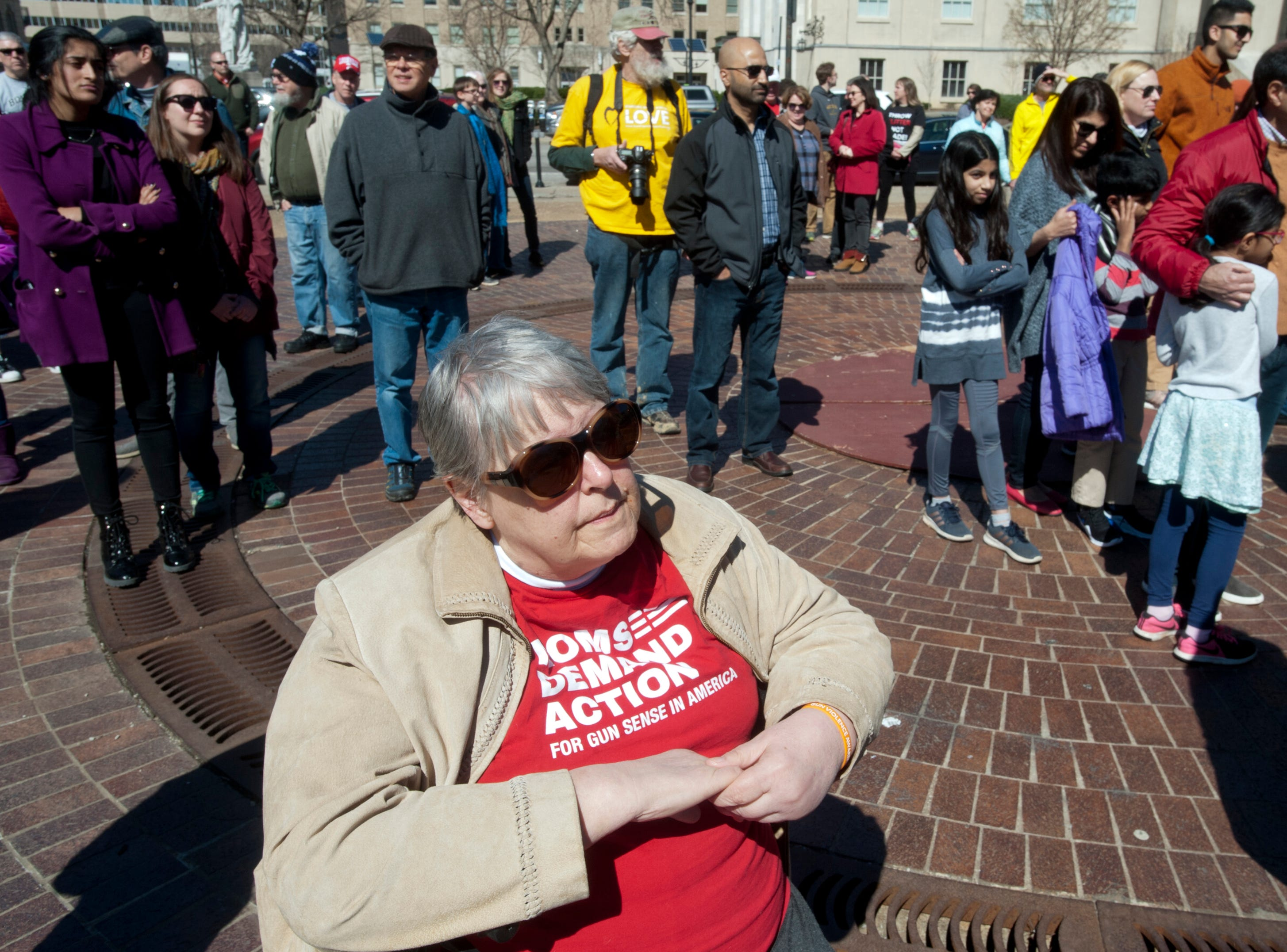 "Patricia Ramey of Schnitzelburg, wears a ""Moms Demand Action For Gun Sense In America"" t-shirt at a vigil in Louisville's Jefferson Square Park to remember the 49 mosque victims in New Zealand as well as those killed in Louisville, in Kentucky, and elsewhere due to religious bigotry and terrorism. Over 150 people participated in the event. 16 March 2019"