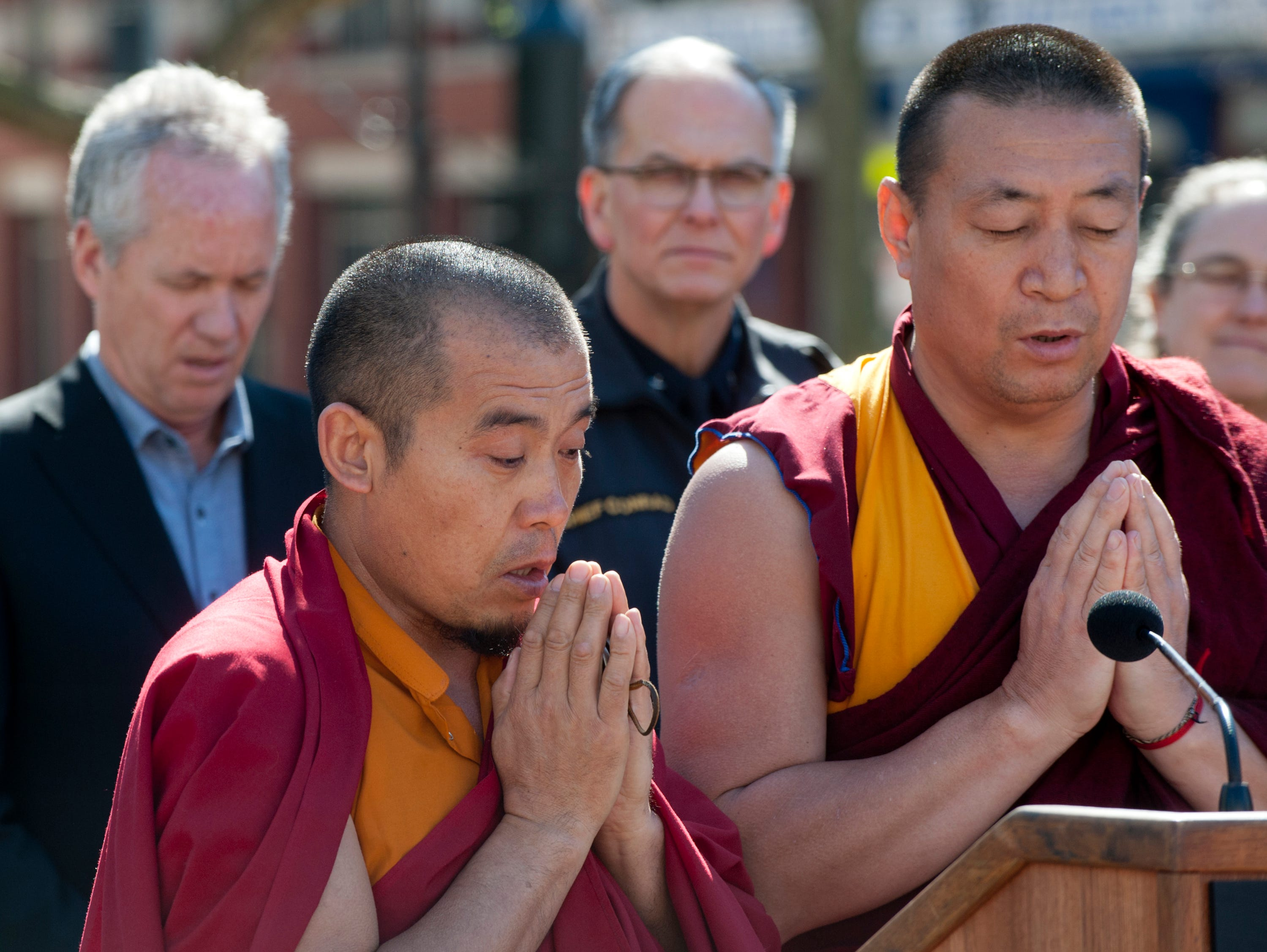 Geshe Sonam, left, and Geshe Gedun, Tibetan Budhist members of the Drepung Gomang Center for Engaging Compassion in St. Matthews, chant a prayer at the vigil.