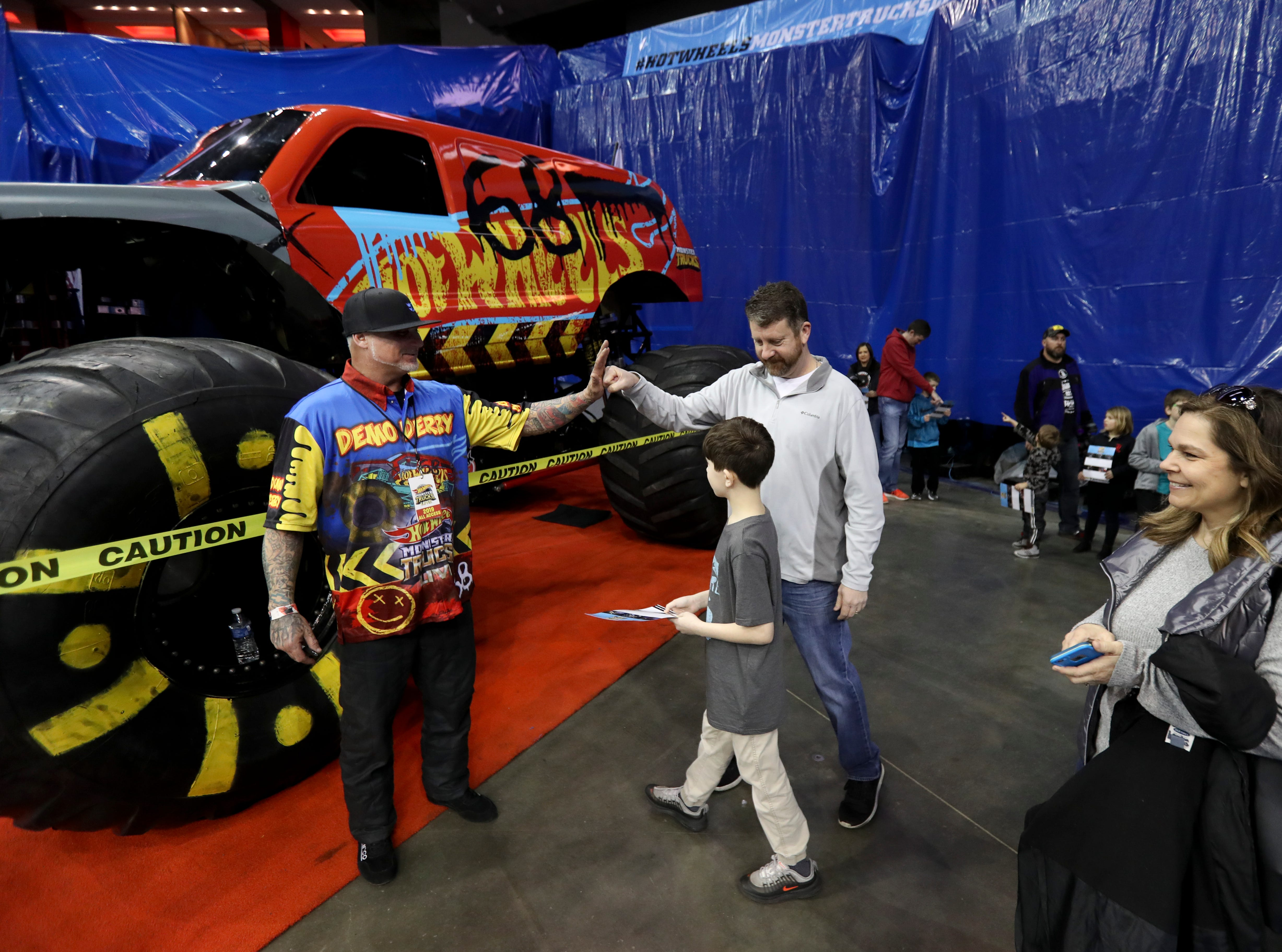 Louisville local Derick Anson, driver of Demo Derby, signs autographs during the Crash Zone Party before the Hot Wheels Monster Trucks show at the KFC Yum Center on March 16.