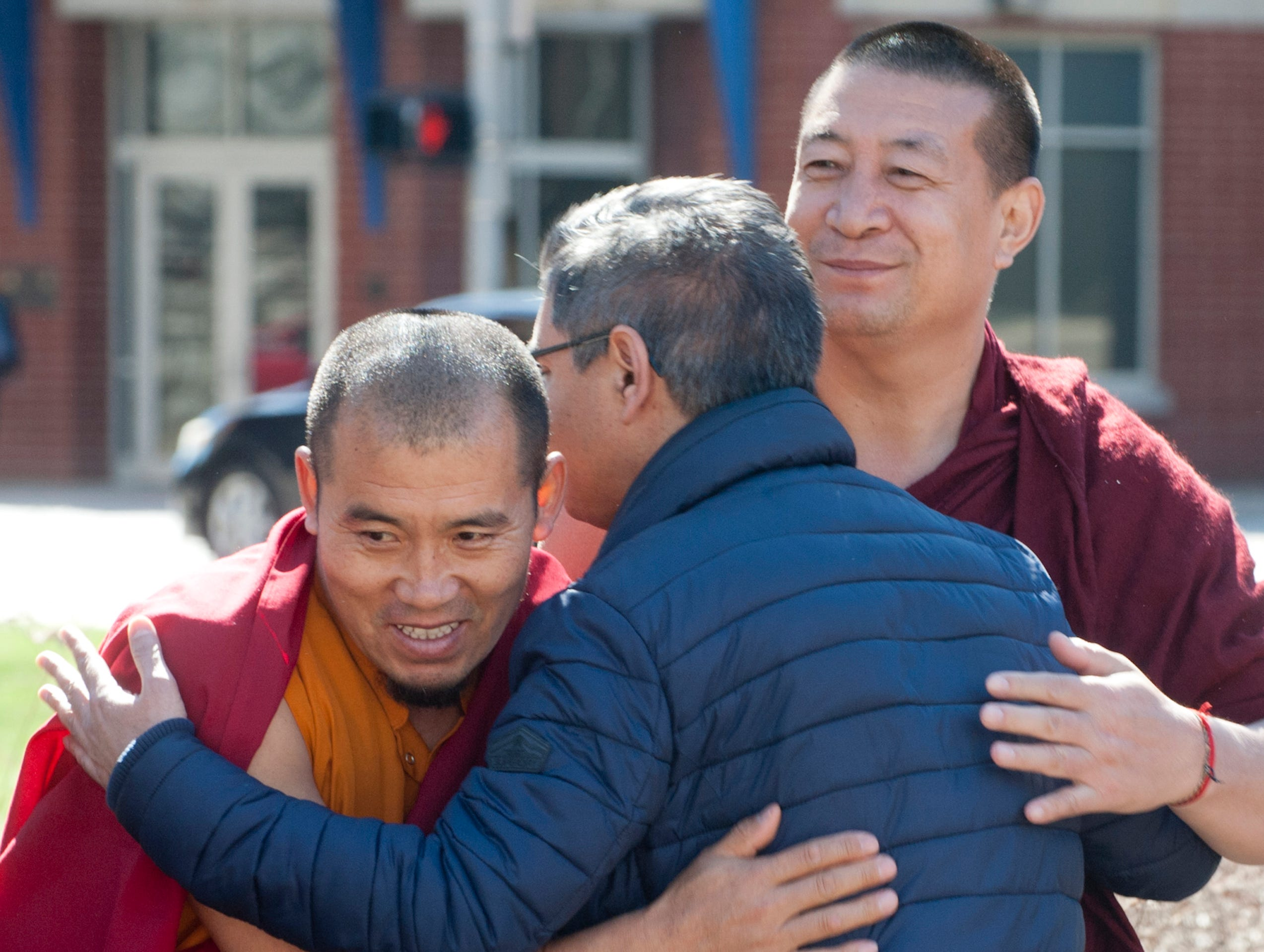 Muslim Americans For Compassion (of Louisville) President Muhammad Babar is hugged by Geshe Sonam, left, and Geshe Gedun, right, Tibetan Buddhist members of the Drepung Gomang Center for Engaging Compassion in St. Matthews, 16 March 2019