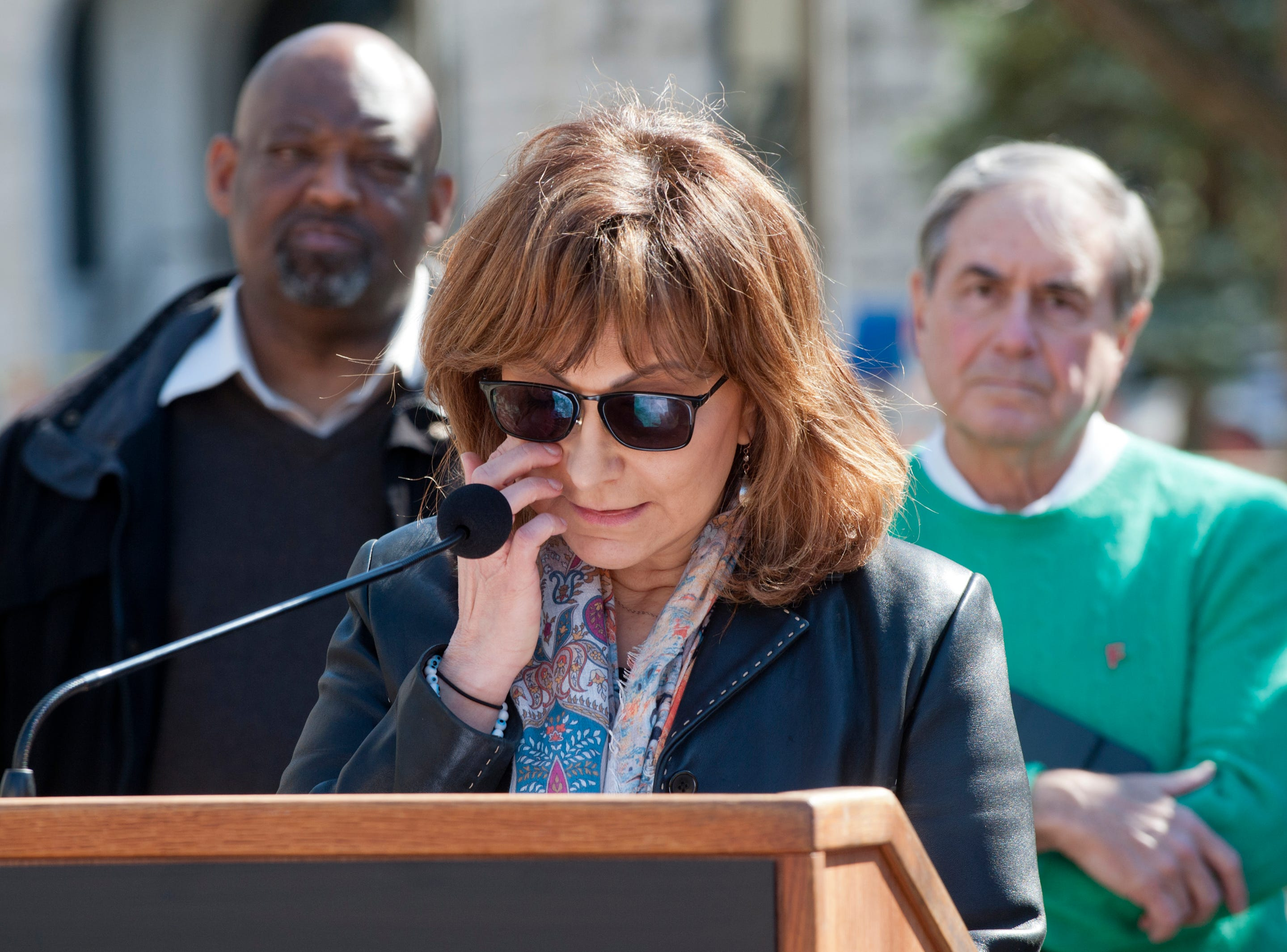 Haleh Karimi, executive director of Louisville's Interfaith Paths to Peace, wipes tears from her eyes as she addresses those gathered at the vigil. Behind her are  James Linton, president of Community Connections Group of Louisville, left, and U.S. Representative John Yarmuth (D-Louisville,) right.