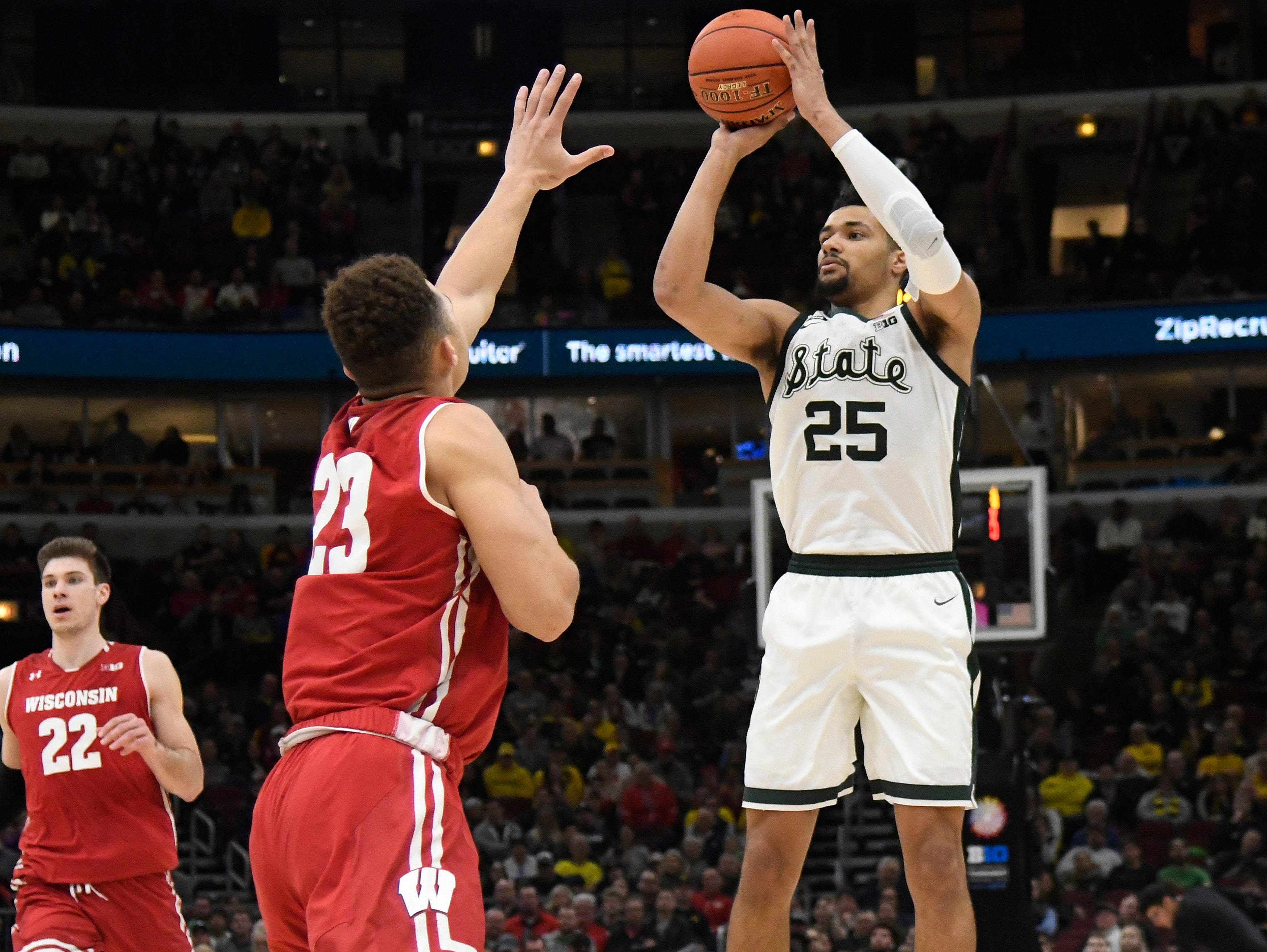 Michigan State Spartans forward Kenny Goins (25) shoots the ball over Wisconsin Badgers guard Kobe King (23) during the second half in the Big Ten conference tournament at United Center.