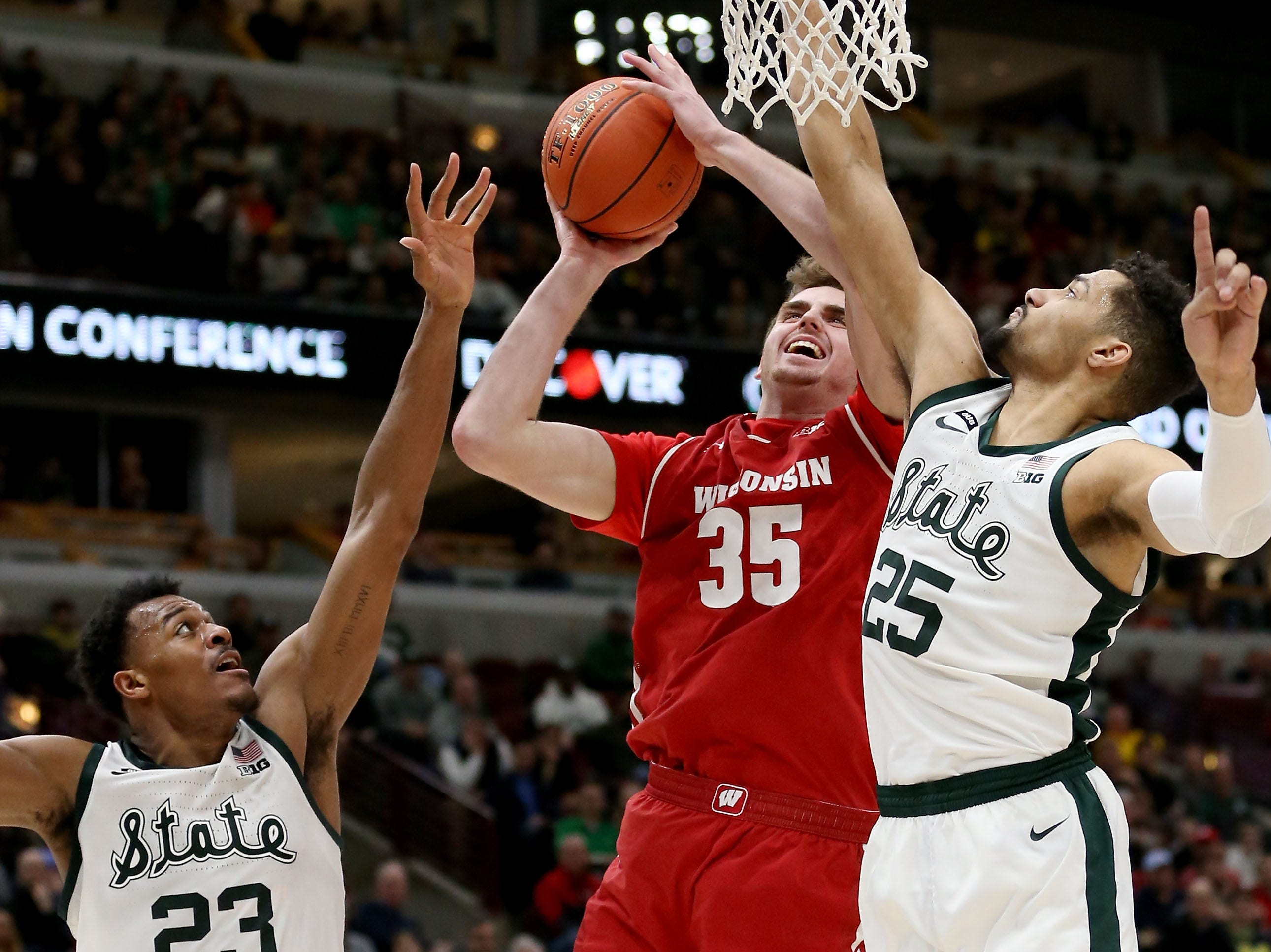Nate Reuvers #35 of the Wisconsin Badgers attempts a shot while being guarded by Xavier Tillman #23 and Kenny Goins #25 of the Michigan State Spartans in the second half during the semifinals of the Big Ten Basketball Tournament at the United Center on March 16, 2019 in Chicago, Illinois.