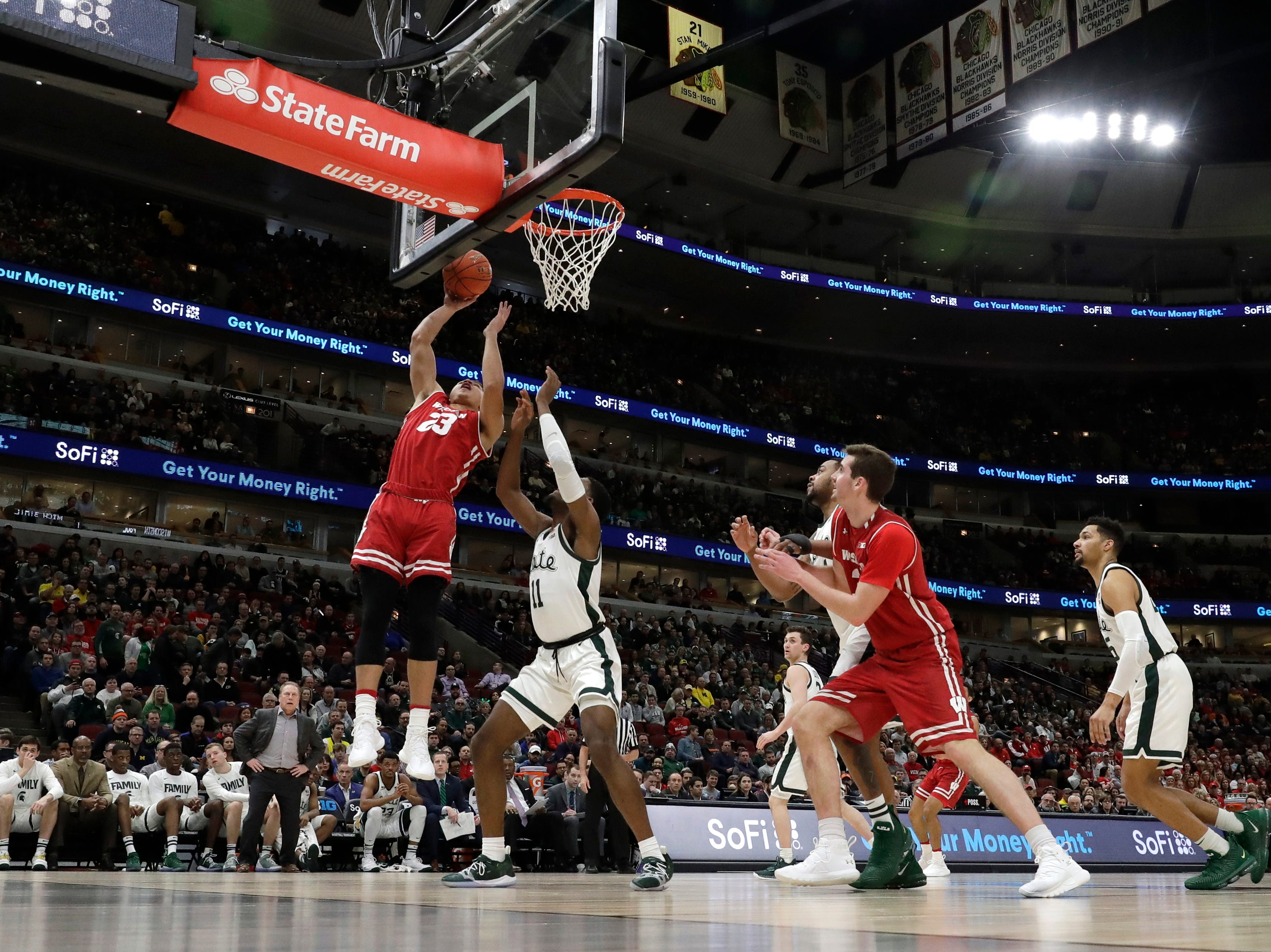 Wisconsin's Kobe King (23) shoot over Michigan State's Aaron Henry (11) during the first half of an NCAA college basketball game in the semifinals of the Big Ten Conference tournament, Saturday, March 16, 2019, in Chicago.