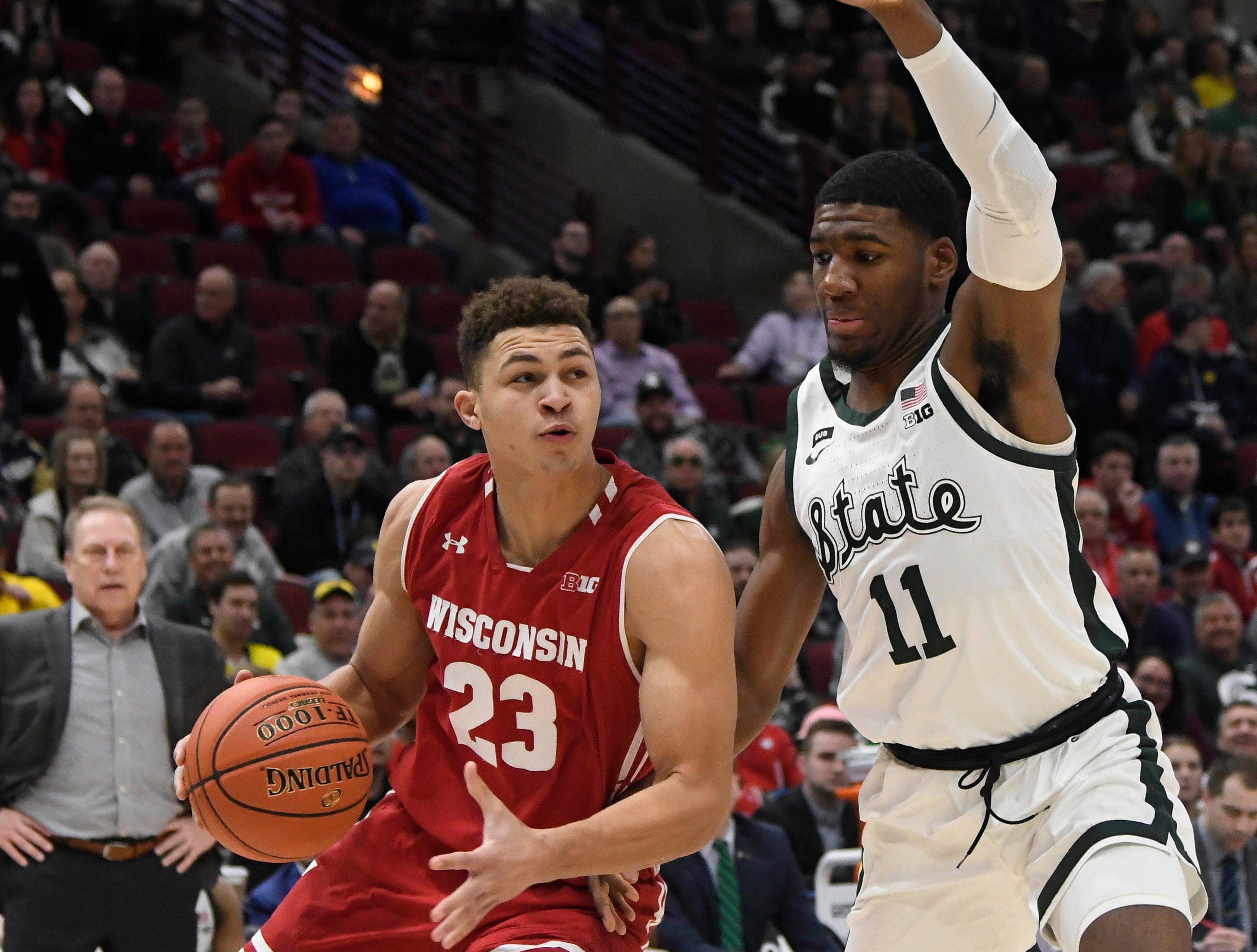 Wisconsin Badgers guard Kobe King (23) dribbles the ball as Michigan State Spartans forward Aaron Henry (11) defends him during the first half in the Big Ten conference tournament at United Center.