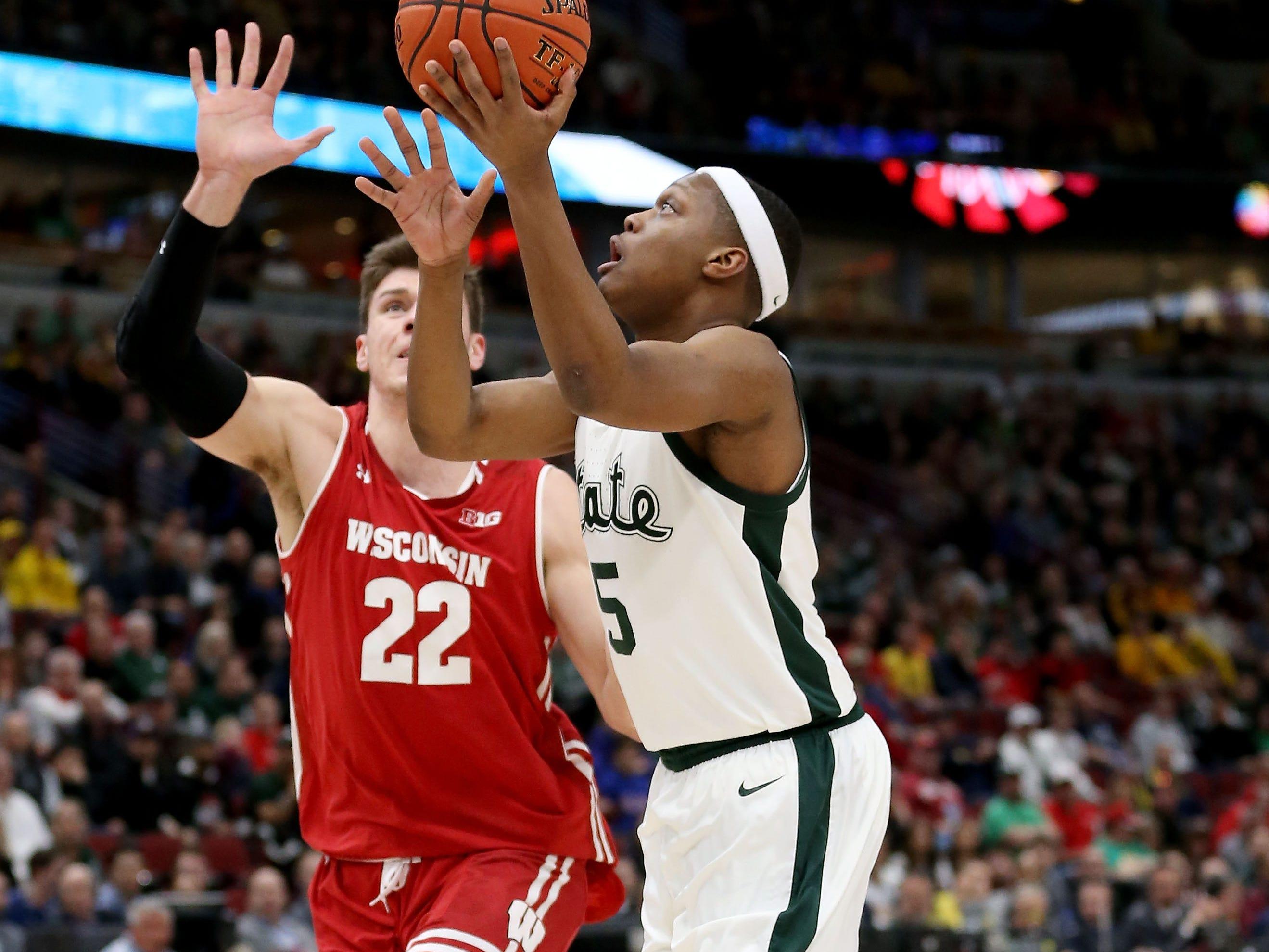 Cassius Winston #5 of the Michigan State Spartans attempts a shot while being guarded by Ethan Happ #22 of the Wisconsin Badgers in the first half during the semifinals of the Big Ten Basketball Tournament at the United Center on March 16, 2019 in Chicago, Illinois.