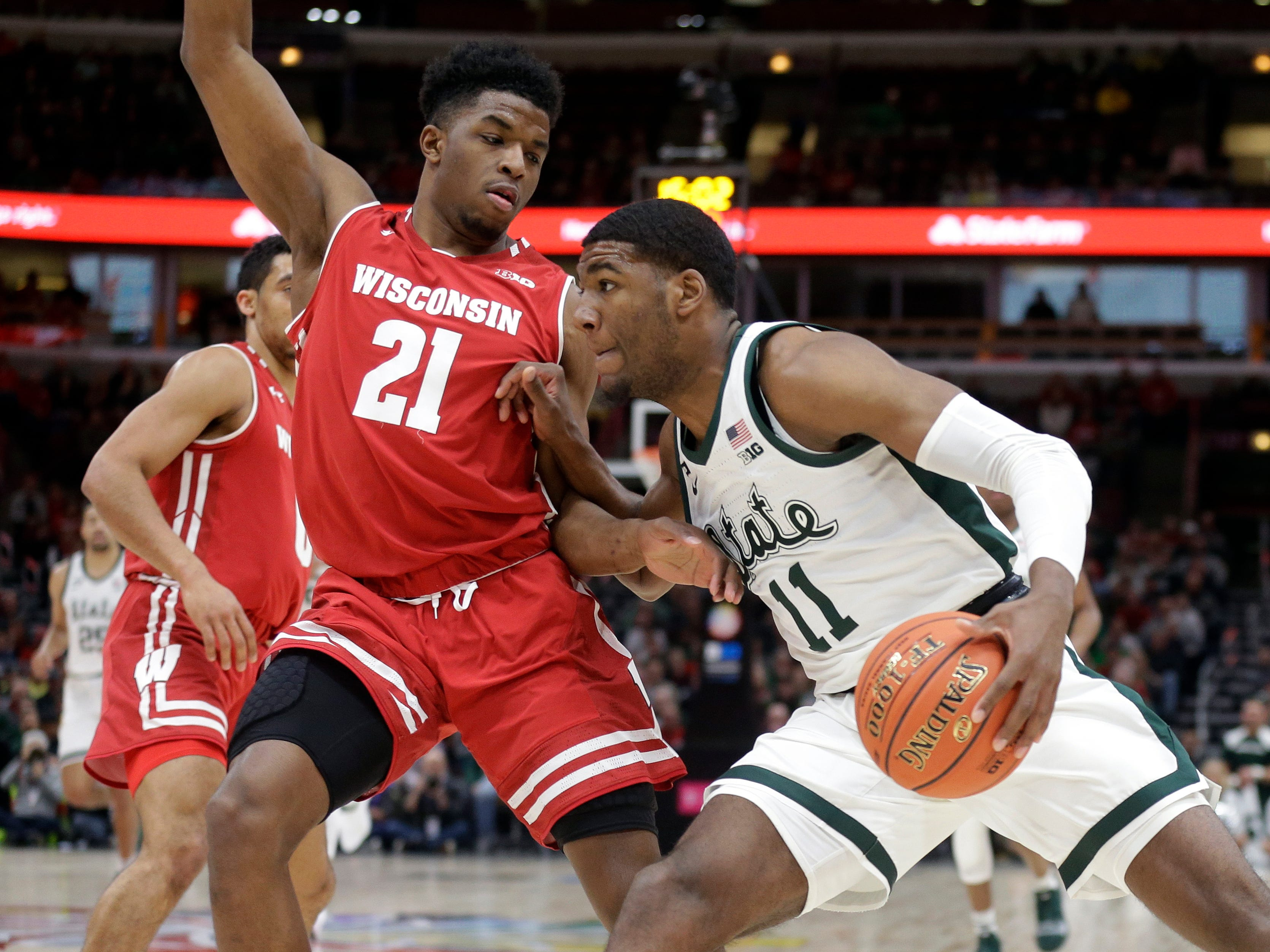 Michigan State's Aaron Henry (11) drives against Wisconsin's Khalil Iverson (21) during the first half of an NCAA college basketball game in the semifinals of the Big Ten Conference tournament, Saturday, March 16, 2019, in Chicago.