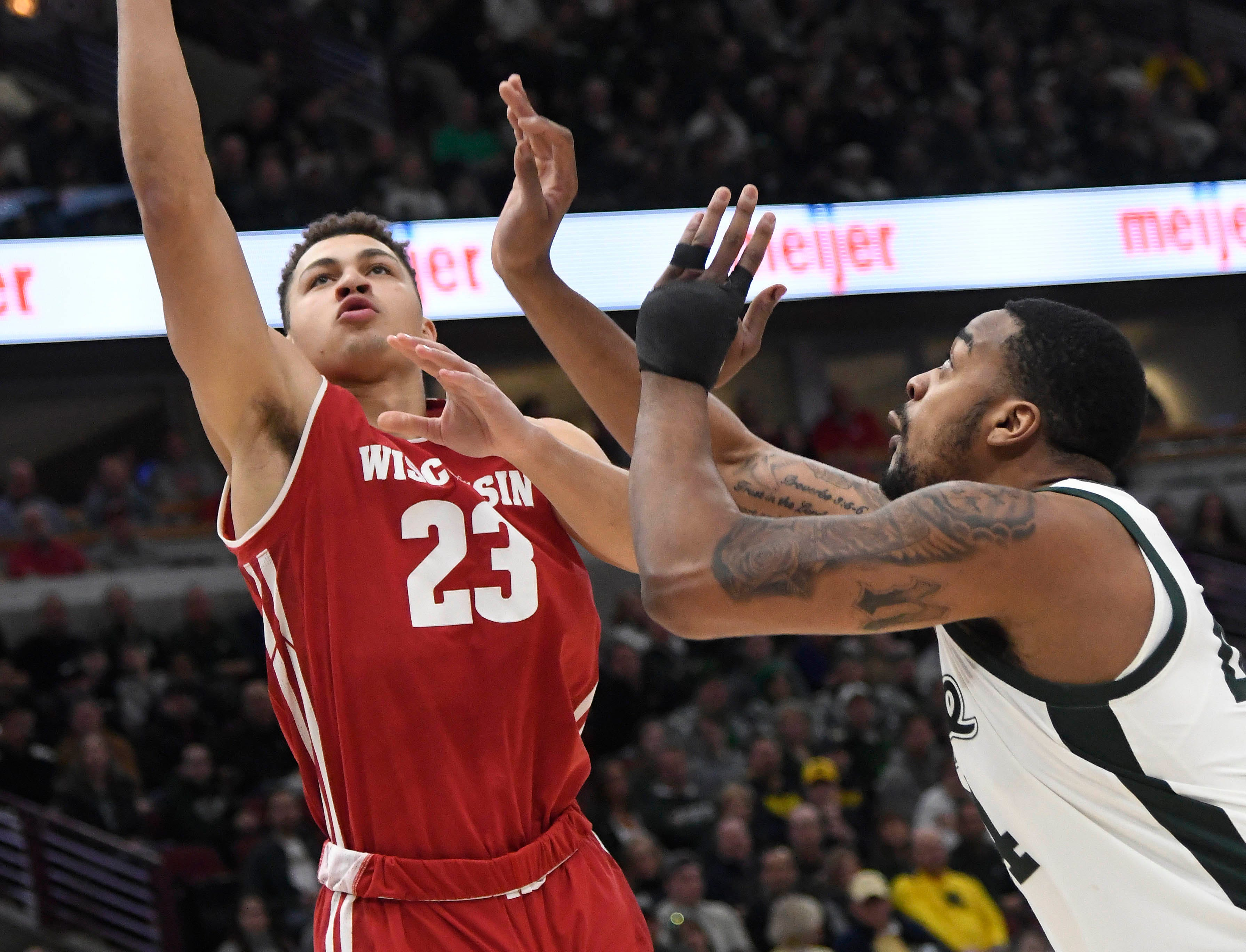 Wisconsin Badgers guard Kobe King (23) shoots the ball over Michigan State Spartans forward Nick Ward (44) during the first half in the Big Ten conference tournament at United Center.