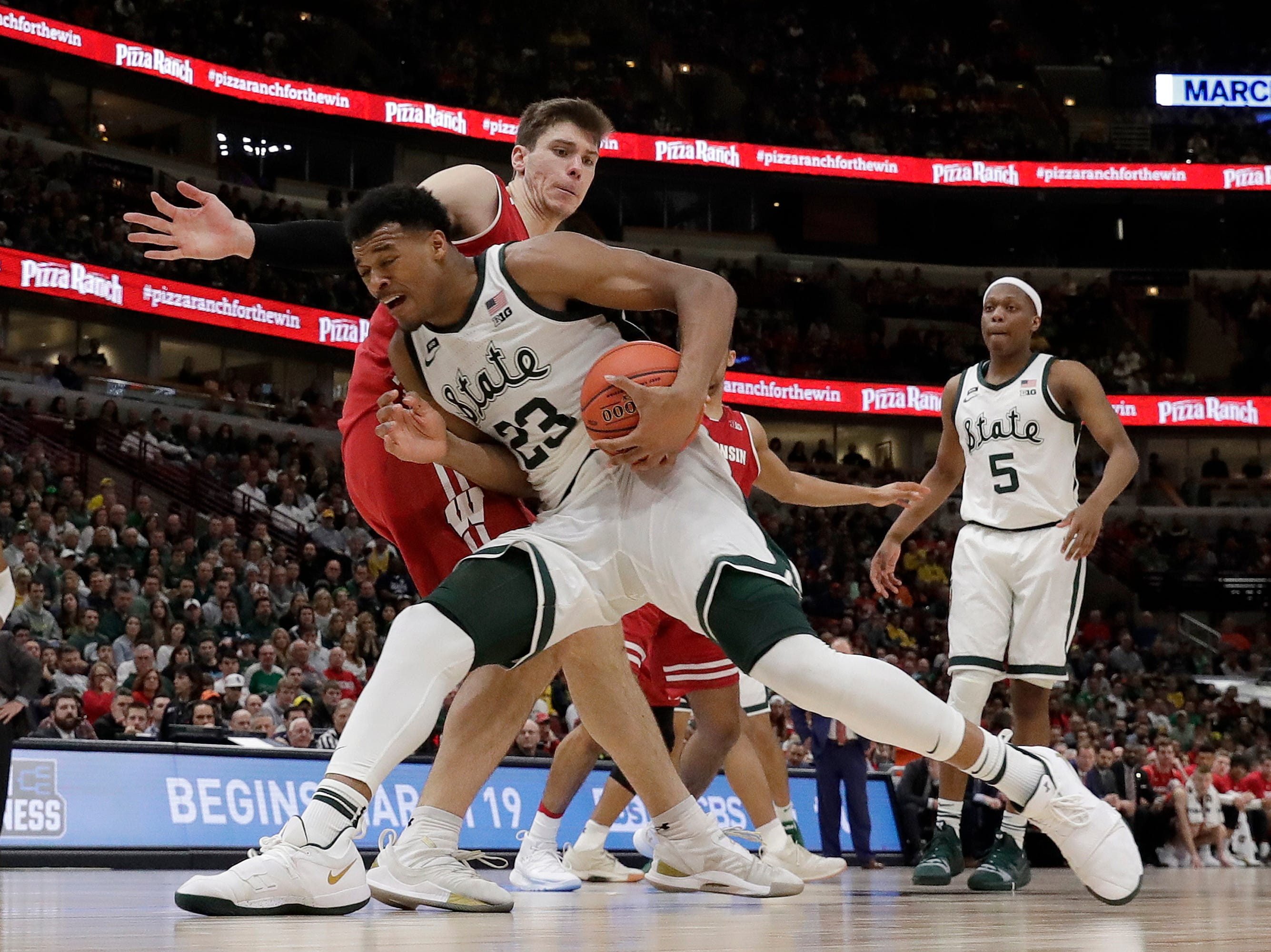 Michigan State's Xavier Tillman (23) drives against Wisconsin's Ethan Happ during the second half of an NCAA college basketball game in the semifinals of the Big Ten Conference tournament, Saturday, March 16, 2019, in Chicago.