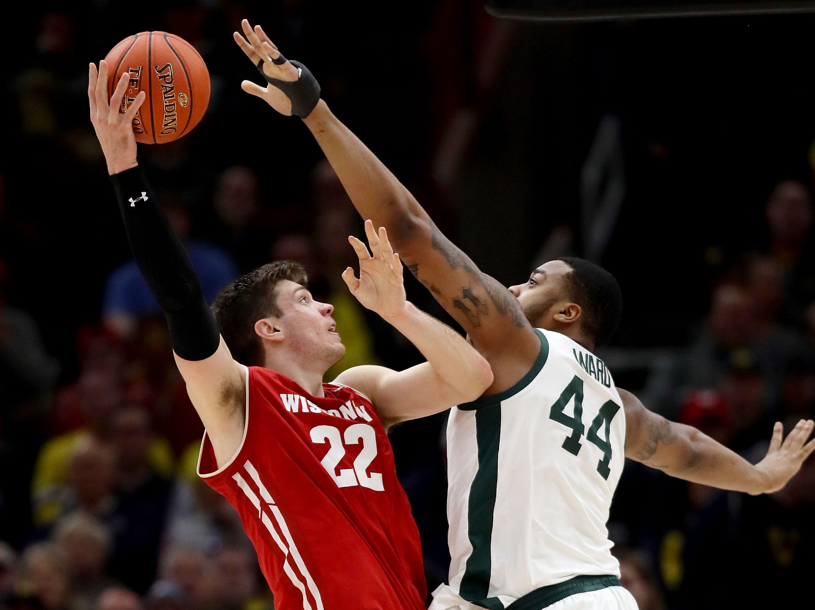 Ethan Happ #22 of the Wisconsin Badgers attempts a shot while being guarded by Nick Ward #44 of the Michigan State Spartans in the second half during the semifinals of the Big Ten Basketball Tournament at the United Center on March 16, 2019 in Chicago, Illinois.