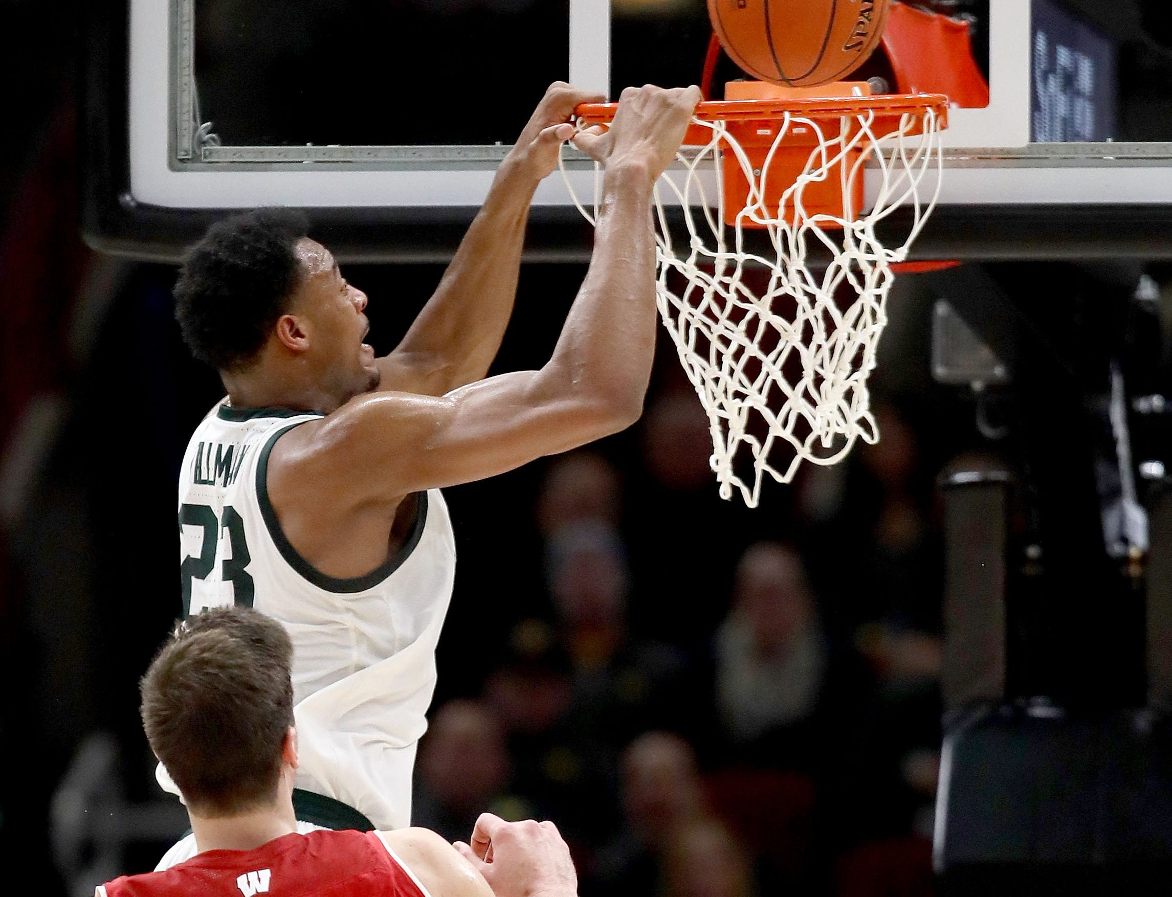 Xavier Tillman #23 of the Michigan State Spartans attempts a dunk past Ethan Happ #22 of the Wisconsin Badgers in the first half during the semifinals of the Big Ten Basketball Tournament at the United Center on March 16, 2019 in Chicago, Illinois.