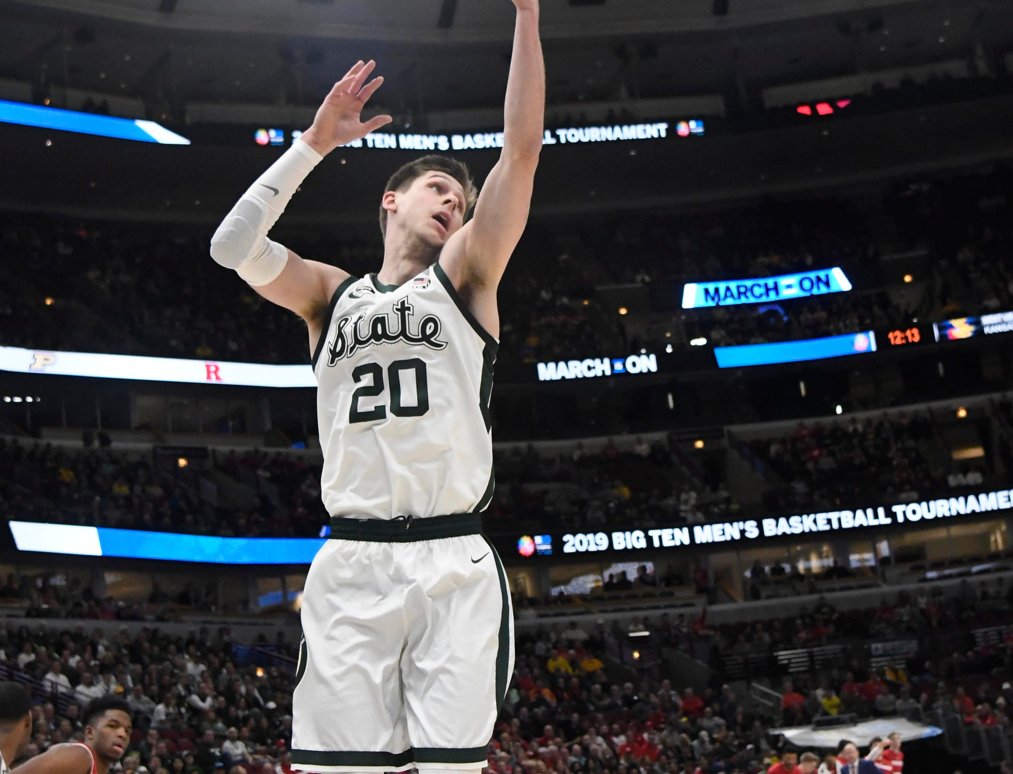 Michigan State Spartans guard Matt McQuaid (20) grabs a rebound against the Wisconsin Badgers during the first half in the Big Ten conference tournament at United Center.