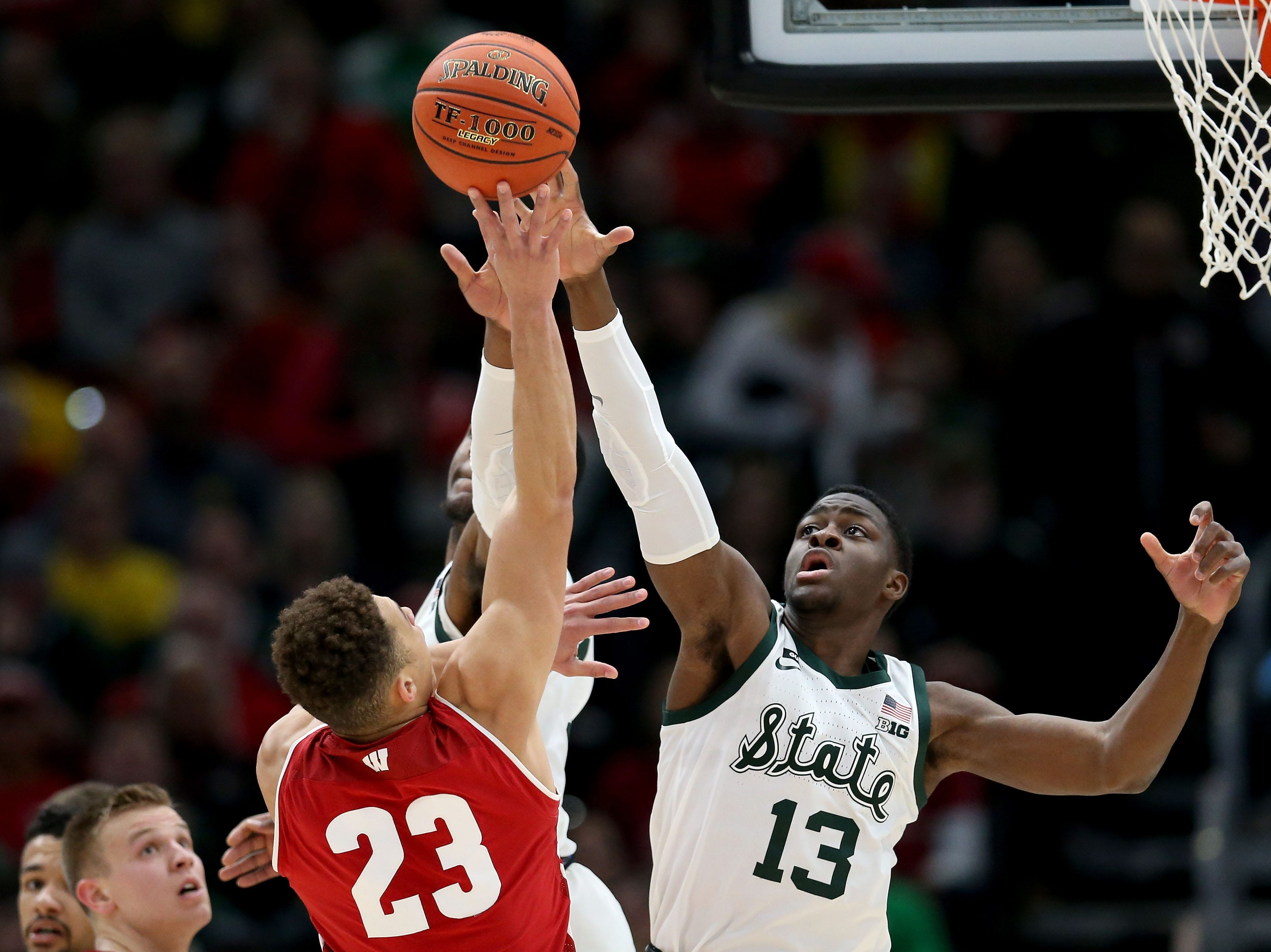 Kobe King #23 of the Wisconsin Badgers attempts a shot while being guarded by Gabe Brown #13 of the Michigan State Spartans in the first half during the semifinals of the Big Ten Basketball Tournament at the United Center on March 16, 2019 in Chicago, Illinois.