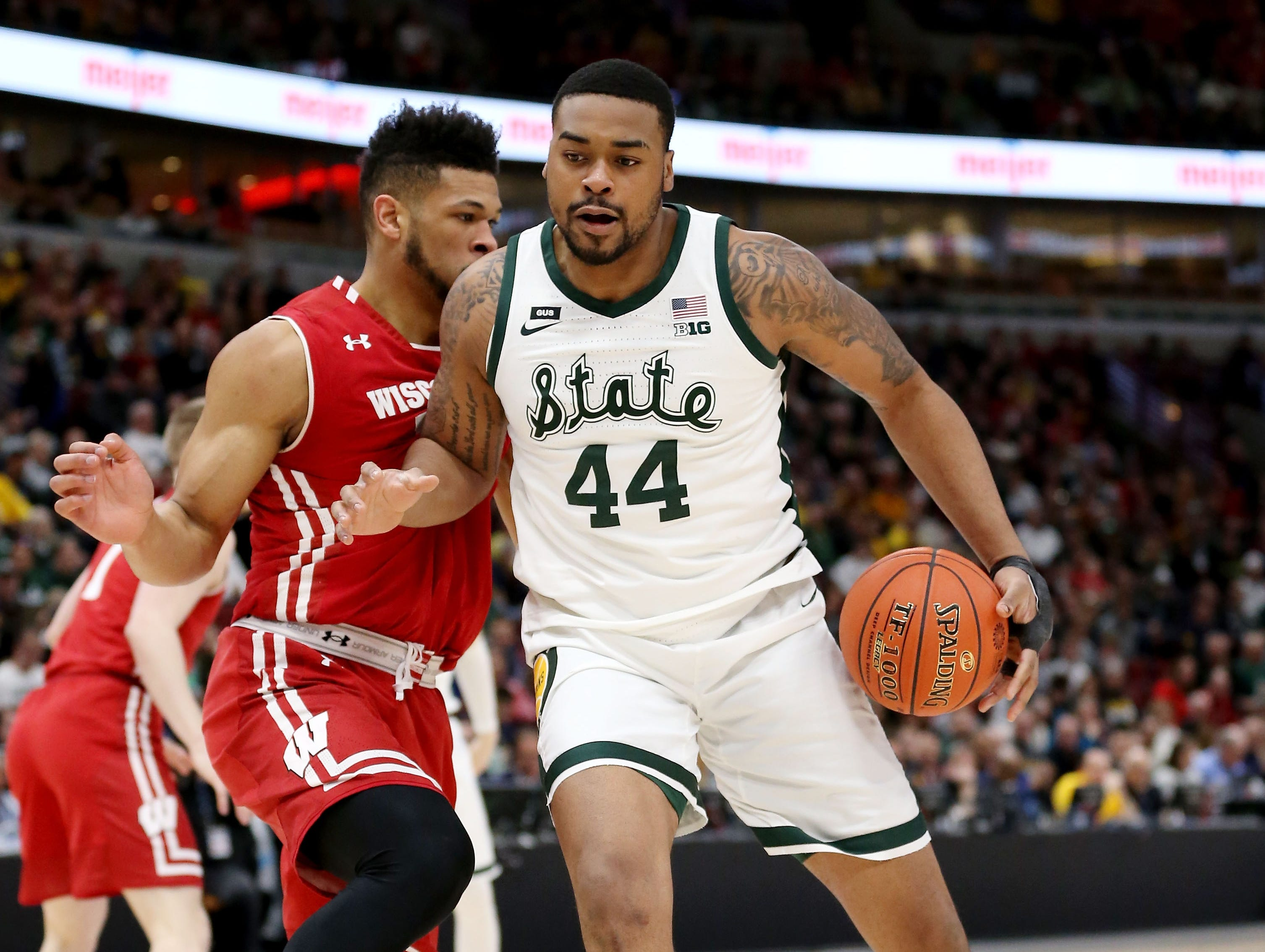 Nick Ward #44 of the Michigan State Spartans dribbles the ball while being guarded by Charles Thomas IV #15 of the Wisconsin Badgers in the first half during the semifinals of the Big Ten Basketball Tournament at the United Center on March 16, 2019 in Chicago, Illinois.