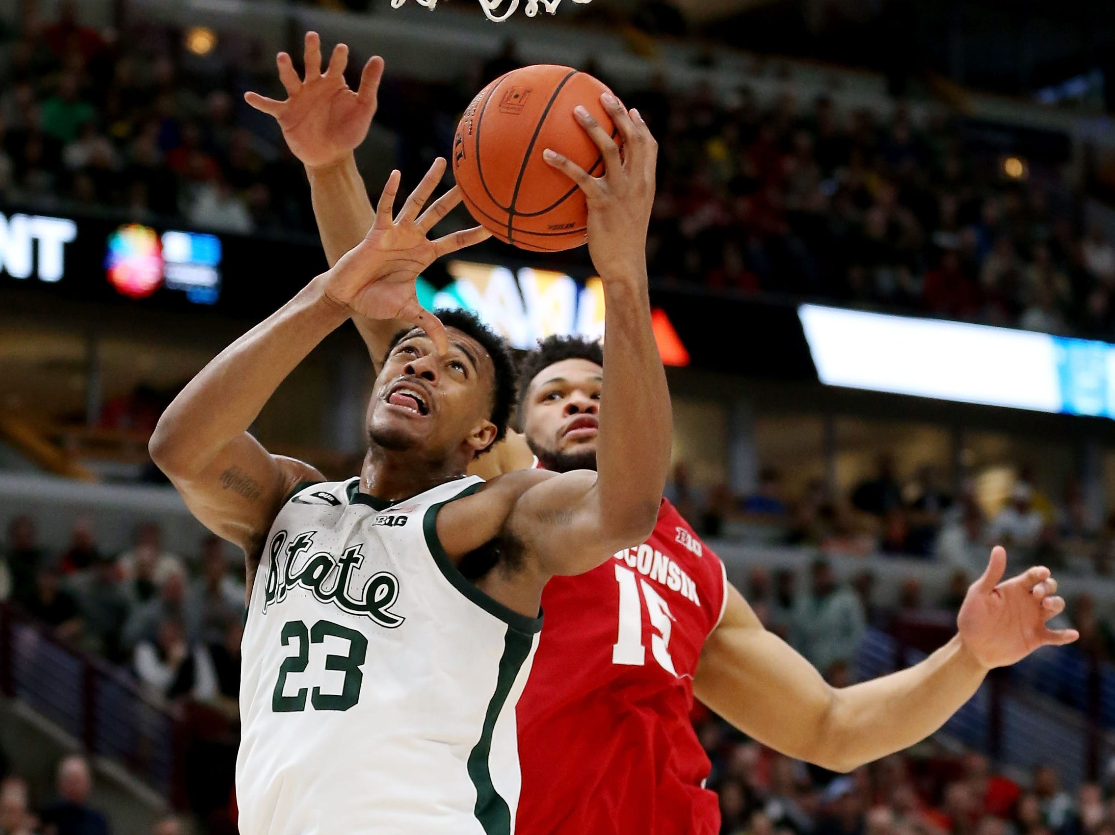 Xavier Tillman #23 of the Michigan State Spartans attempts a shot while being guarded by Charles Thomas IV #15 of the Wisconsin Badgers in the first half during the semifinals of the Big Ten Basketball Tournament at the United Center on March 16, 2019 in Chicago, Illinois.
