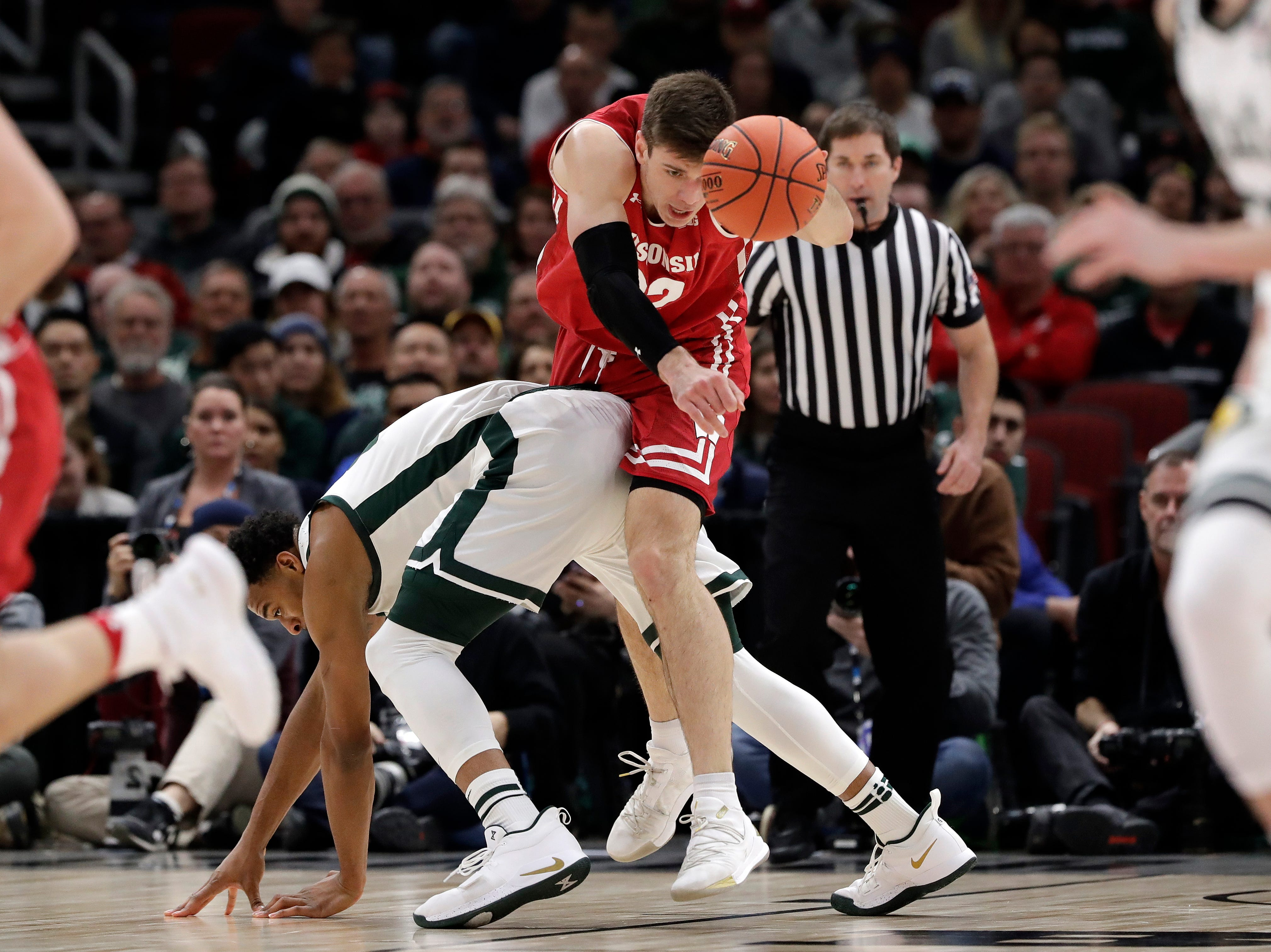 Wisconsin's Ethan Happ (22) chases the ball over Michigan's Xavier Tillman during the first half of an NCAA college basketball game in the semifinals of the Big Ten Conference tournament, Saturday, March 16, 2019, in Chicago.