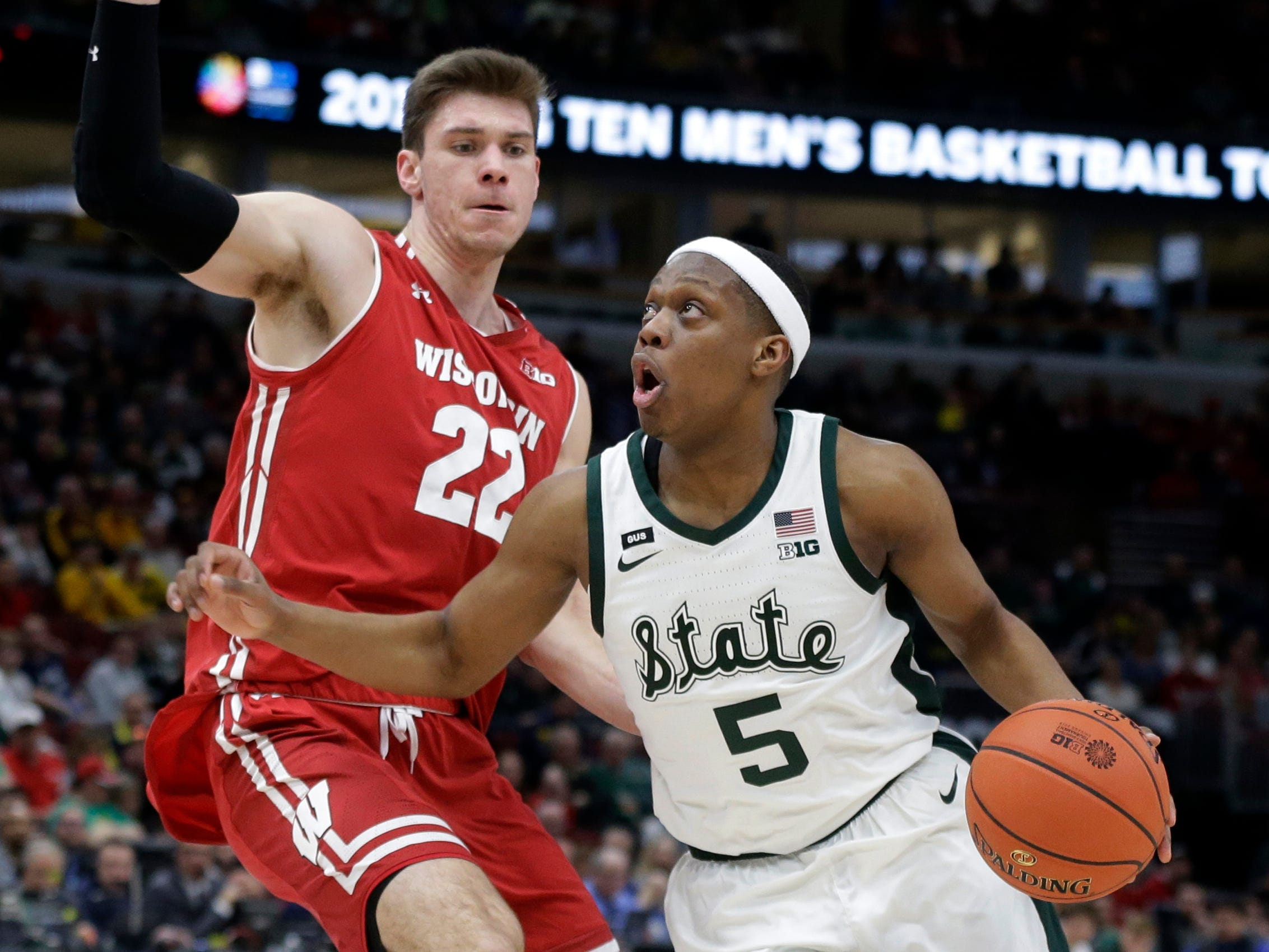 Michigan State's Cassius Winston (5) drives past Wisconsin's Ethan Happ (22) during the first half of an NCAA college basketball game in the semifinals of the Big Ten Conference tournament, Saturday, March 16, 2019, in Chicago.