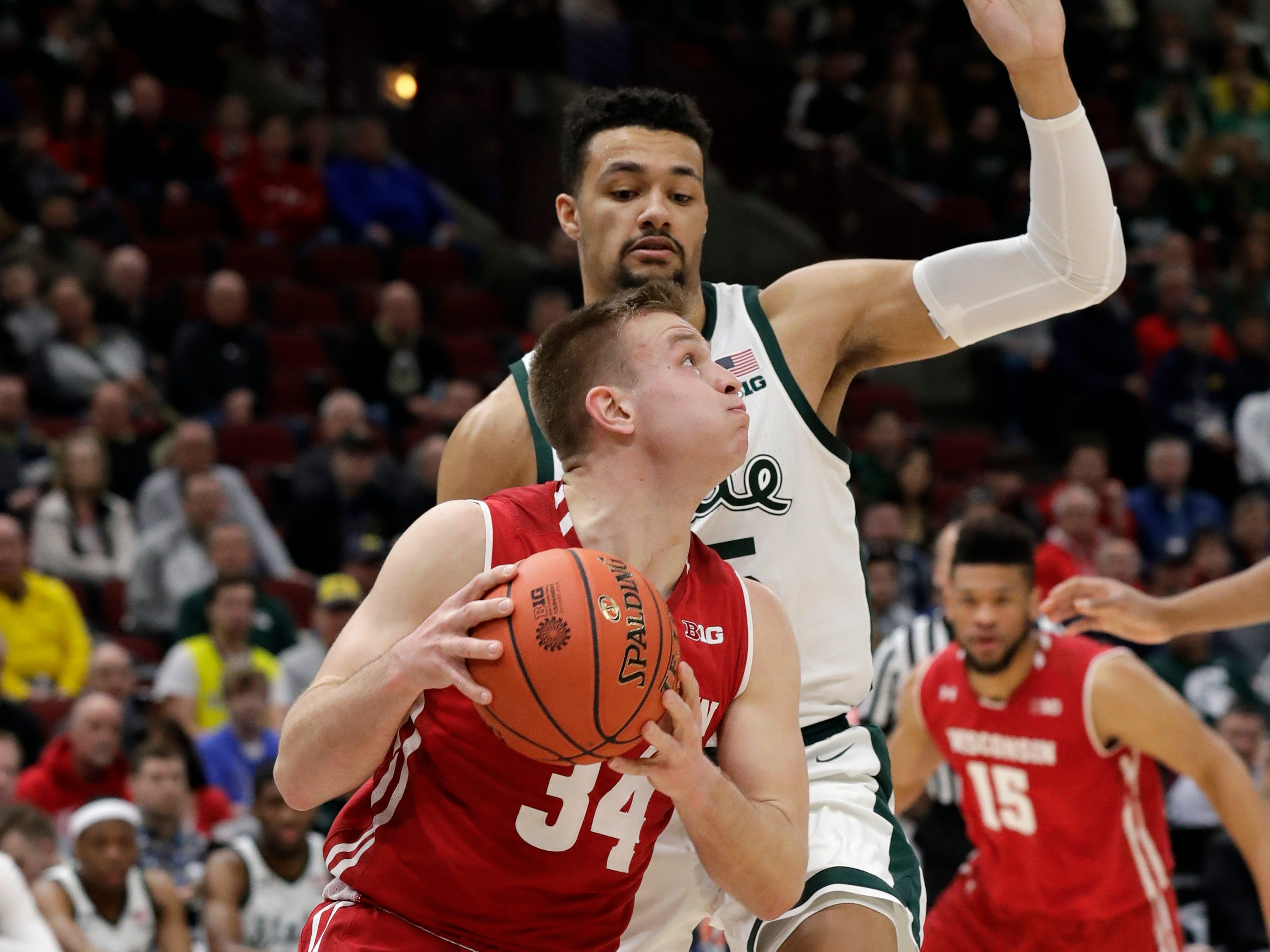 Wisconsin's Carter Higginbottom (4) drives against Michigan State's Kenny Goins (25) during the first half of an NCAA college basketball game in the semifinals of the Big Ten Conference tournament, Saturday, March 16, 2019, in Chicago.