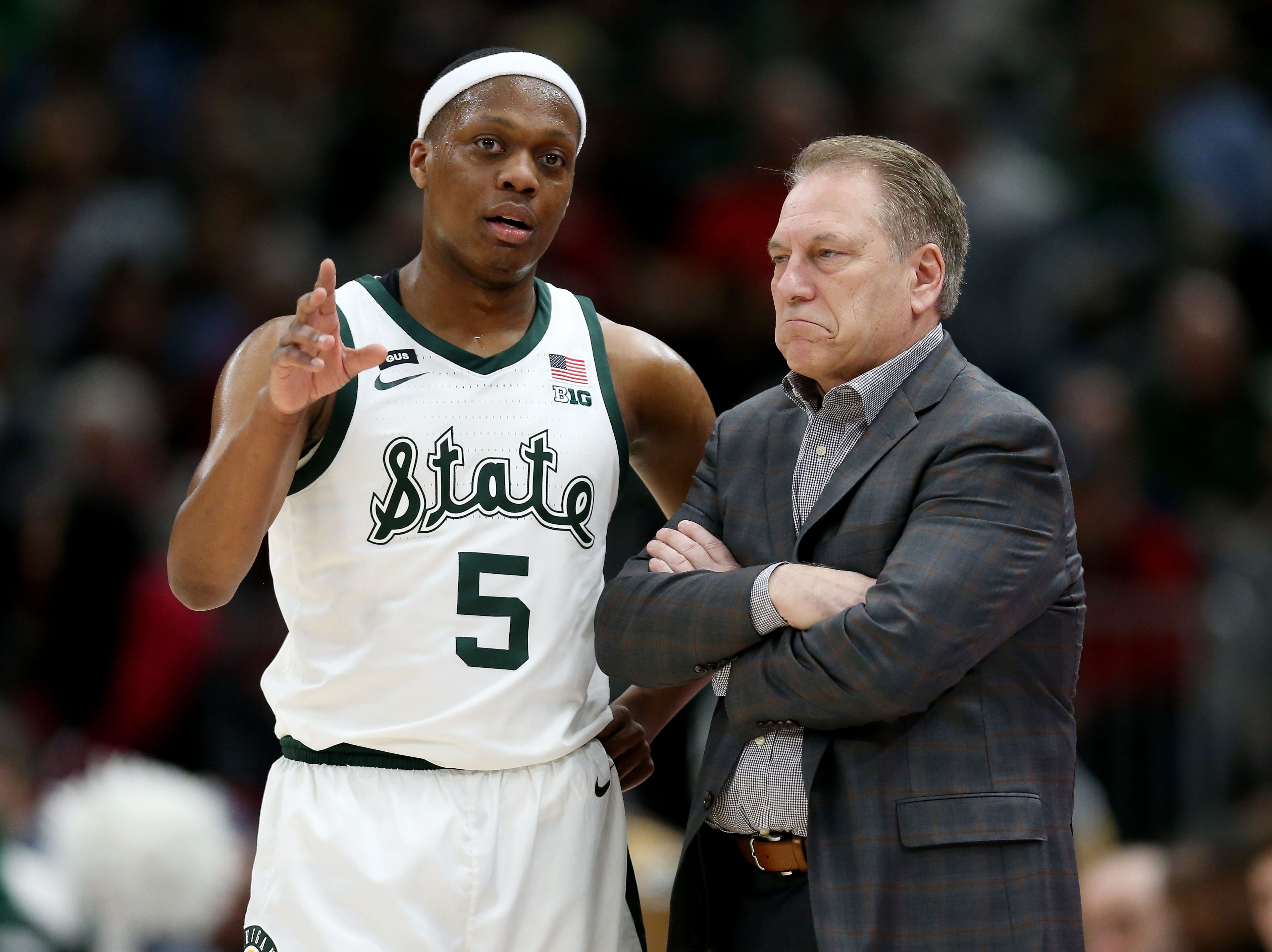 Cassius Winston #5 of the Michigan State Spartans meets with head coach Tom Izzo in the first half against the Wisconsin Badgers during the semifinals of the Big Ten Basketball Tournament at the United Center on March 16, 2019 in Chicago, Illinois.