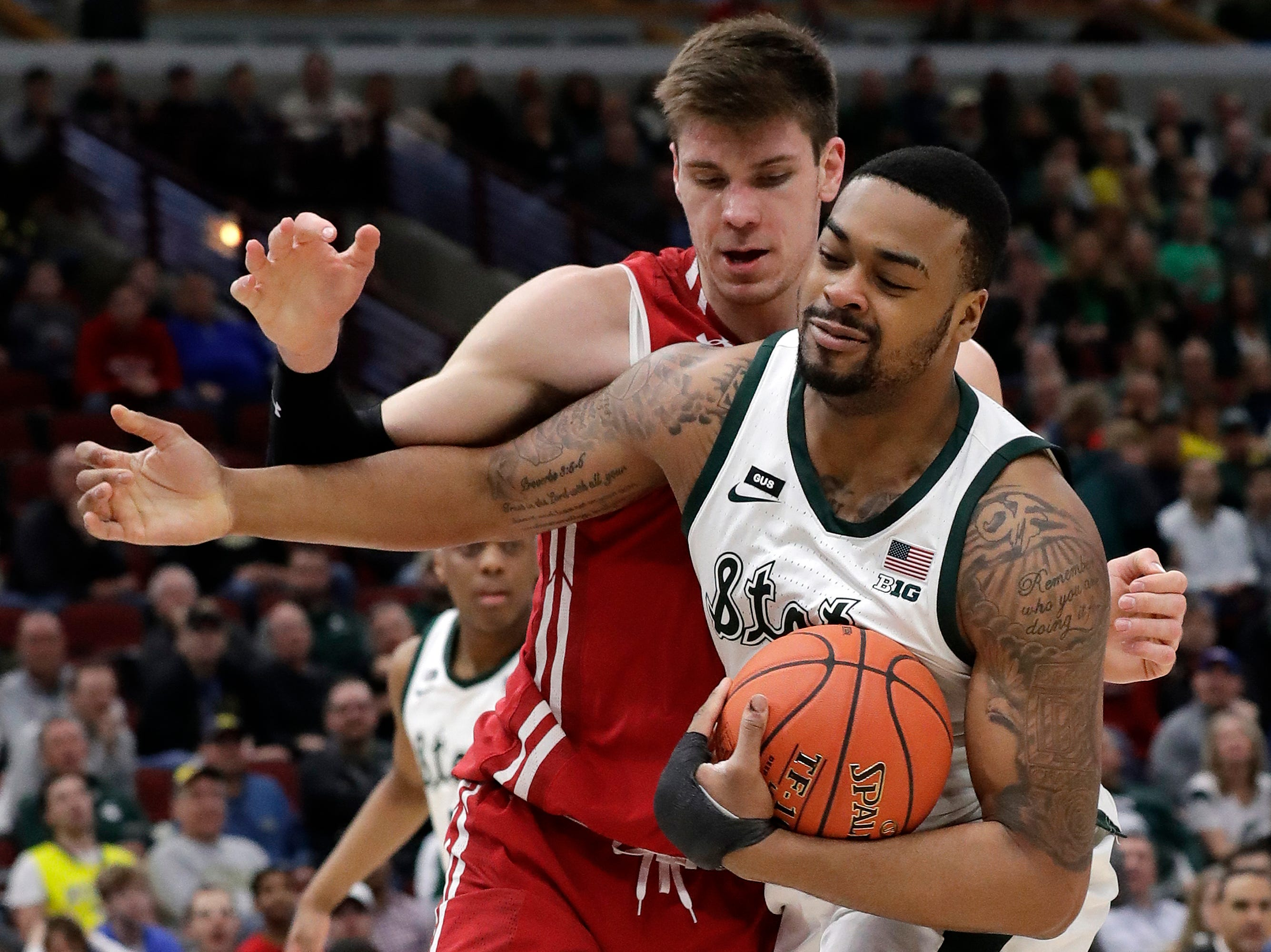 Michigan State's Nick Ward, right, battles for a loose ball against Wisconsin's Ethan Happ during the first half of an NCAA college basketball game in the semifinals of the Big Ten Conference tournament, Saturday, March 16, 2019, in Chicago.