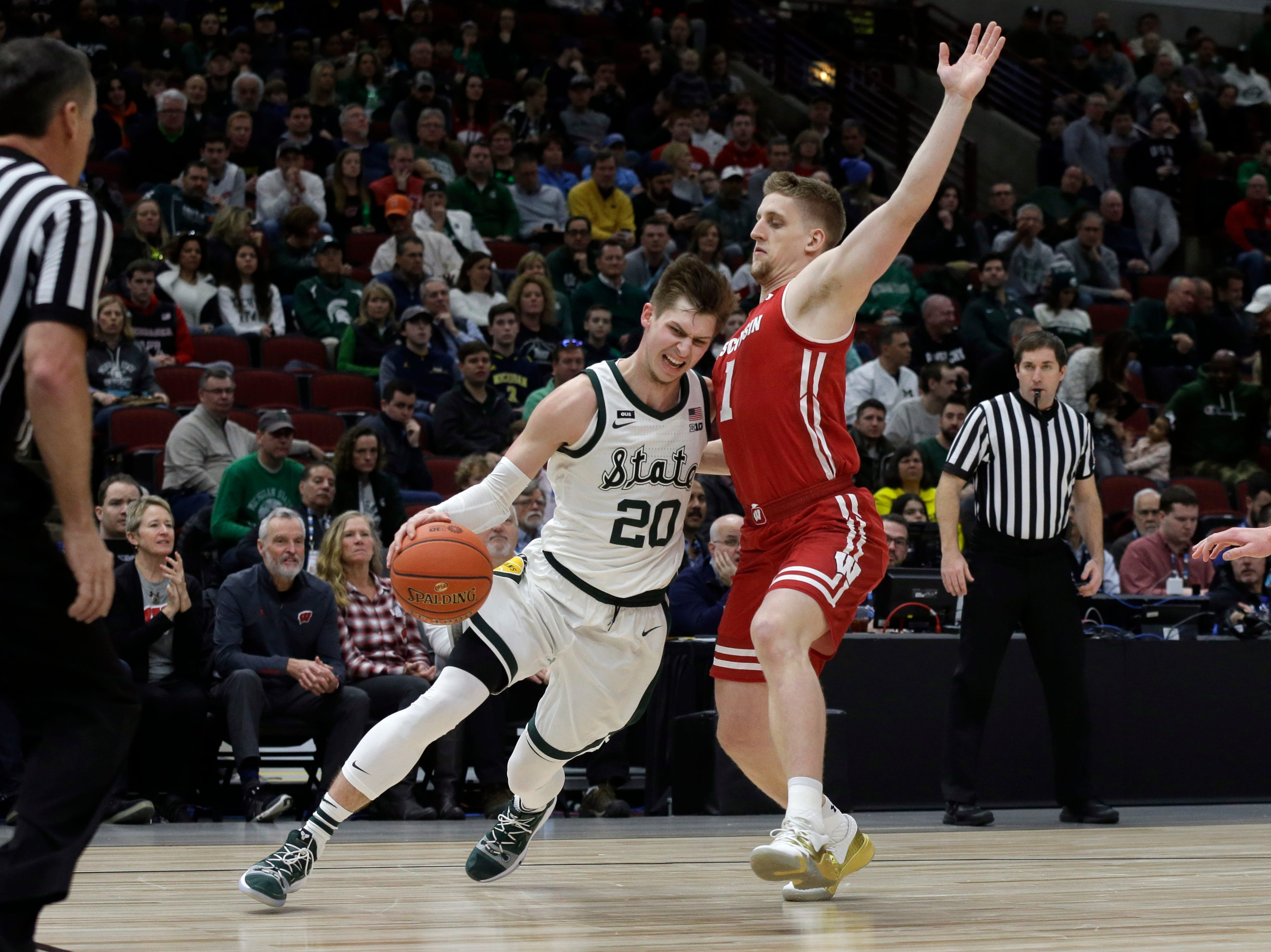 Michigan State's Matt McQuaid (20) drives against Wisconsin's Brevin Pritzl (1) during the first half of an NCAA college basketball game in the semifinals of the Big Ten Conference tournament, Saturday, March 16, 2019, in Chicago.