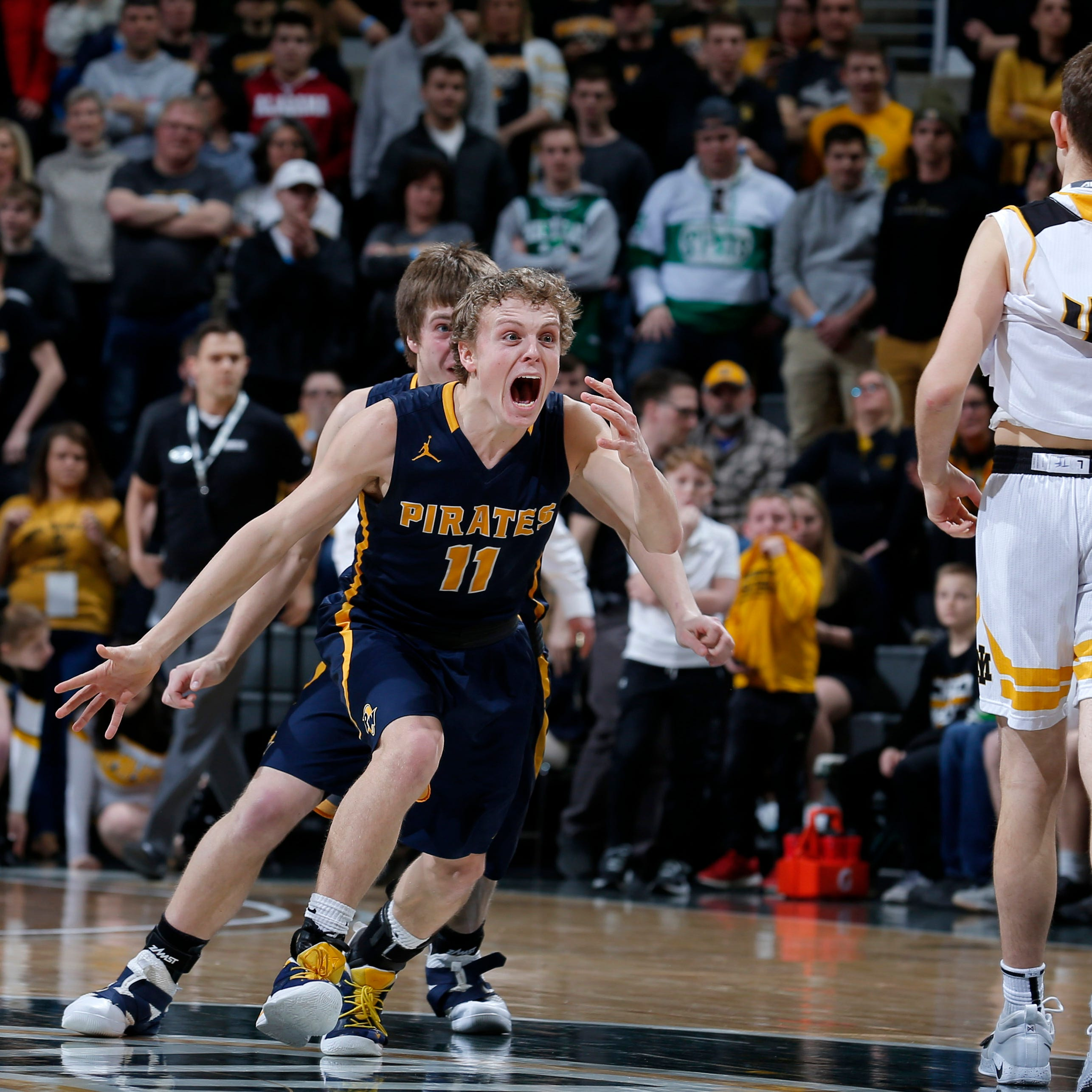 Pewamo-Westphalia's Collin Trierweiler (11) and Nathan Wirth, rear, celebrate as time expires in their MHSAA championship win over Iron Mountain, Saturday, March 16, 2019, in East Lansing, Mich. P-W won 53-52.