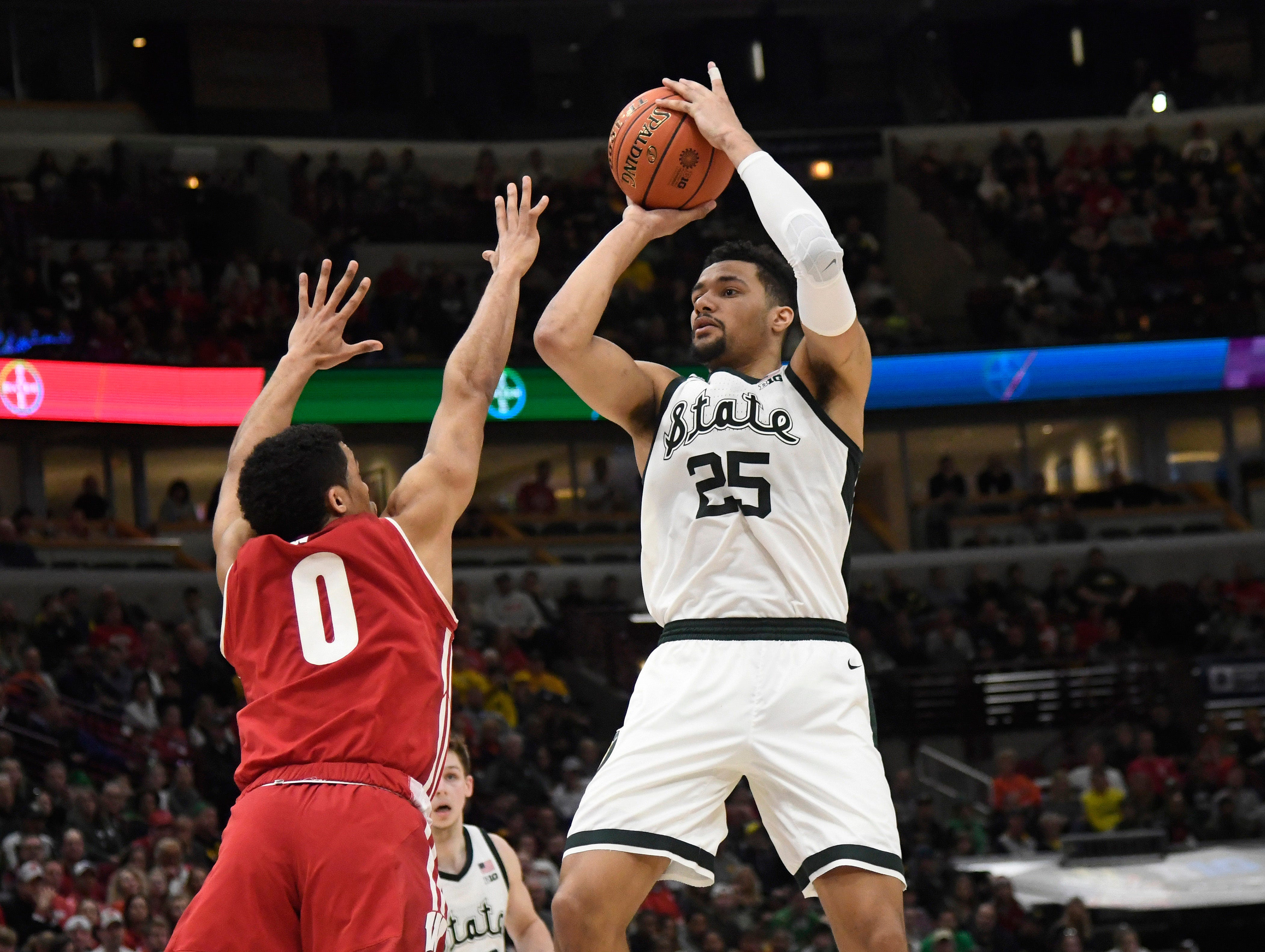 Michigan State Spartans forward Kenny Goins (25) shoots the ball over Wisconsin Badgers guard D'Mitrik Trice (0) during the second half in the Big Ten conference tournament at United Center.