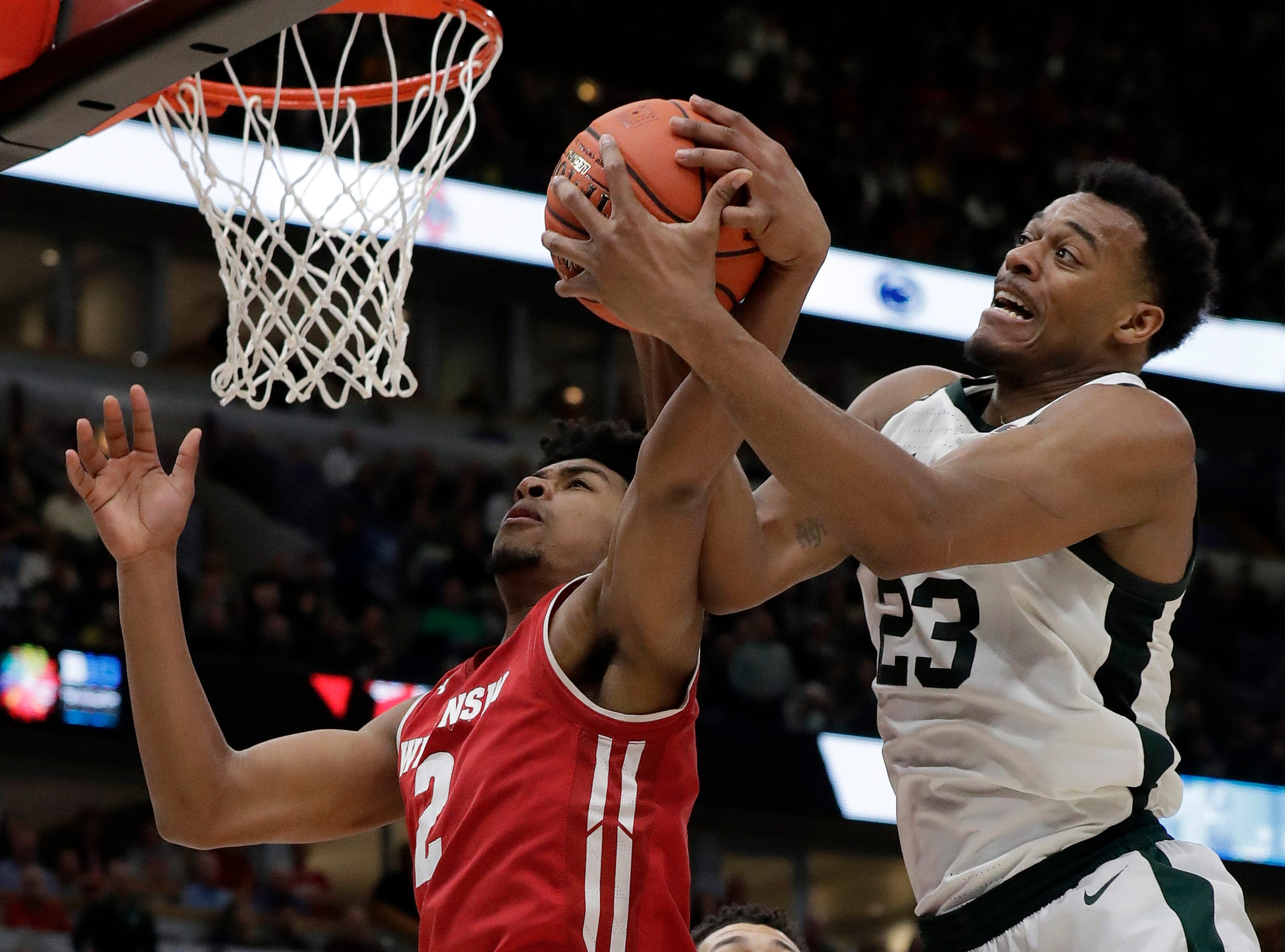 Wisconsin's Aleem Ford (2) and Michigan State's Xavier Tillman (23) battle for a rebound during the second half of an NCAA college basketball game in the semifinals of the Big Ten Conference tournament, Saturday, March 16, 2019, in Chicago.