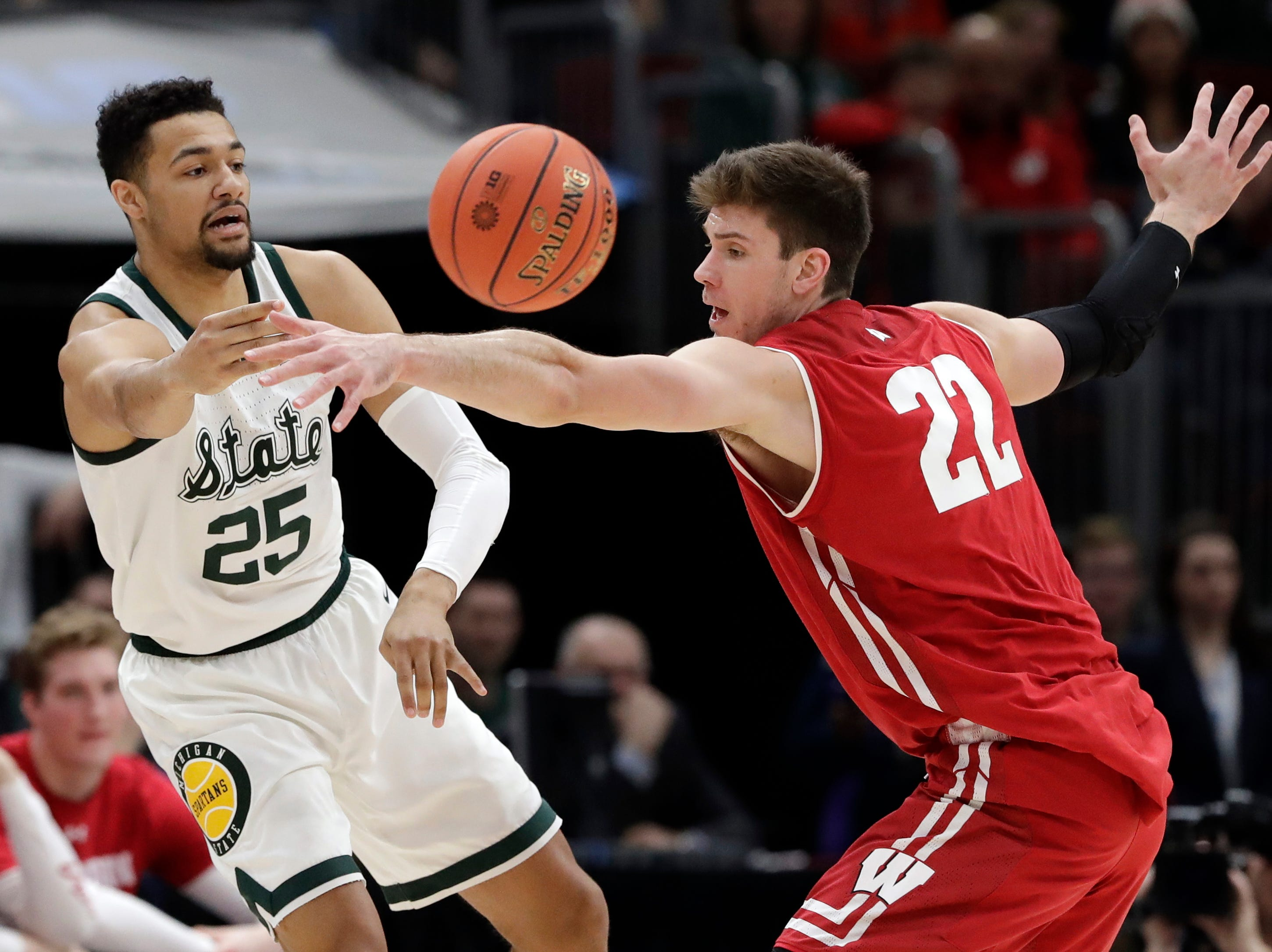 Michigan State's Kenny Goins (25) pass the ball around Wisconsin's Ethan Happ (22) during the first half of an NCAA college basketball game in the semifinals of the Big Ten Conference tournament, Saturday, March 16, 2019, in Chicago.