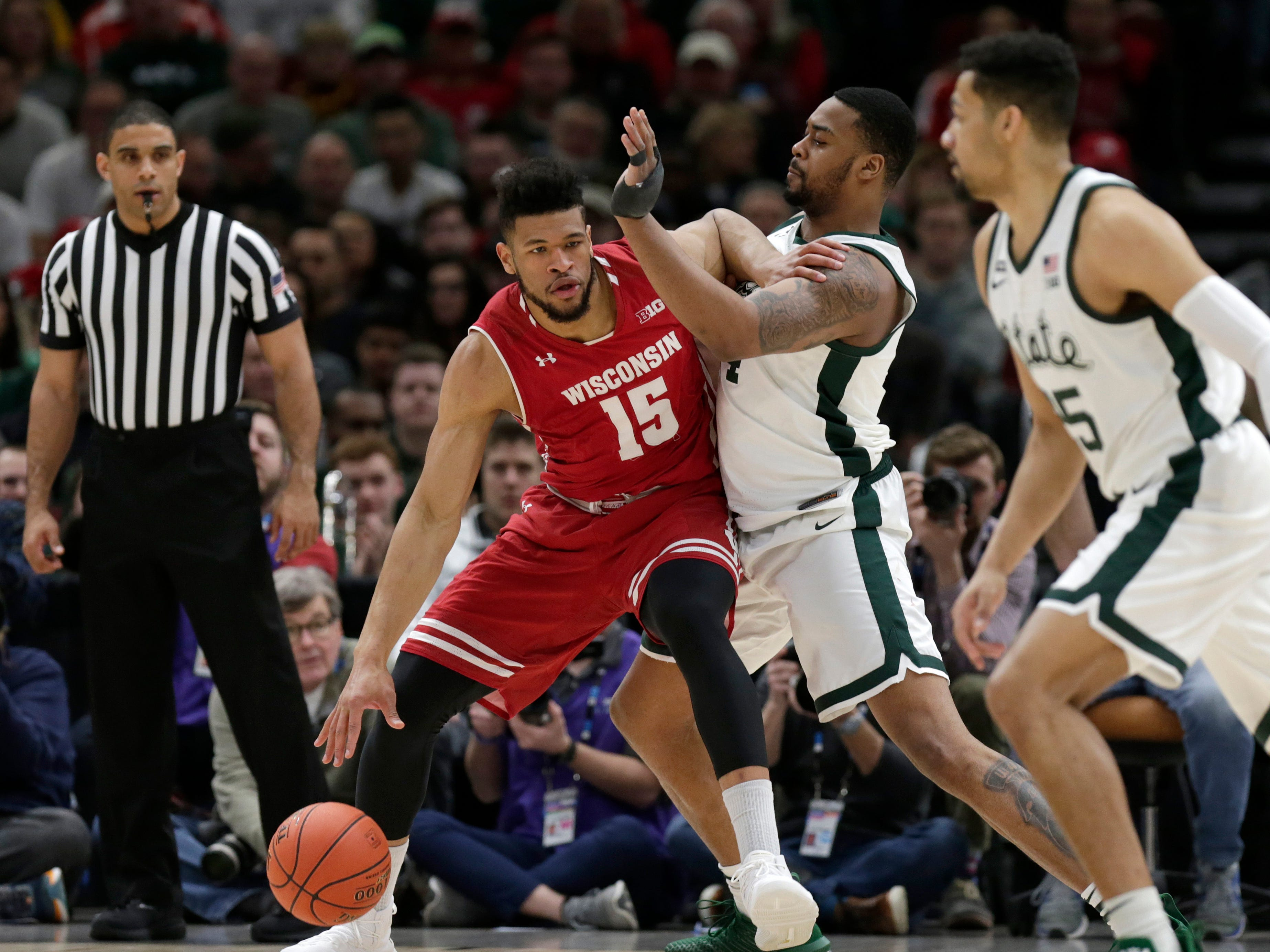 Wisconsin's Charles Thomas IV (15) derives against Michigan State's Nick Ward during the first half of an NCAA college basketball game in the semifinals of the Big Ten Conference tournament, Saturday, March 16, 2019, in Chicago.