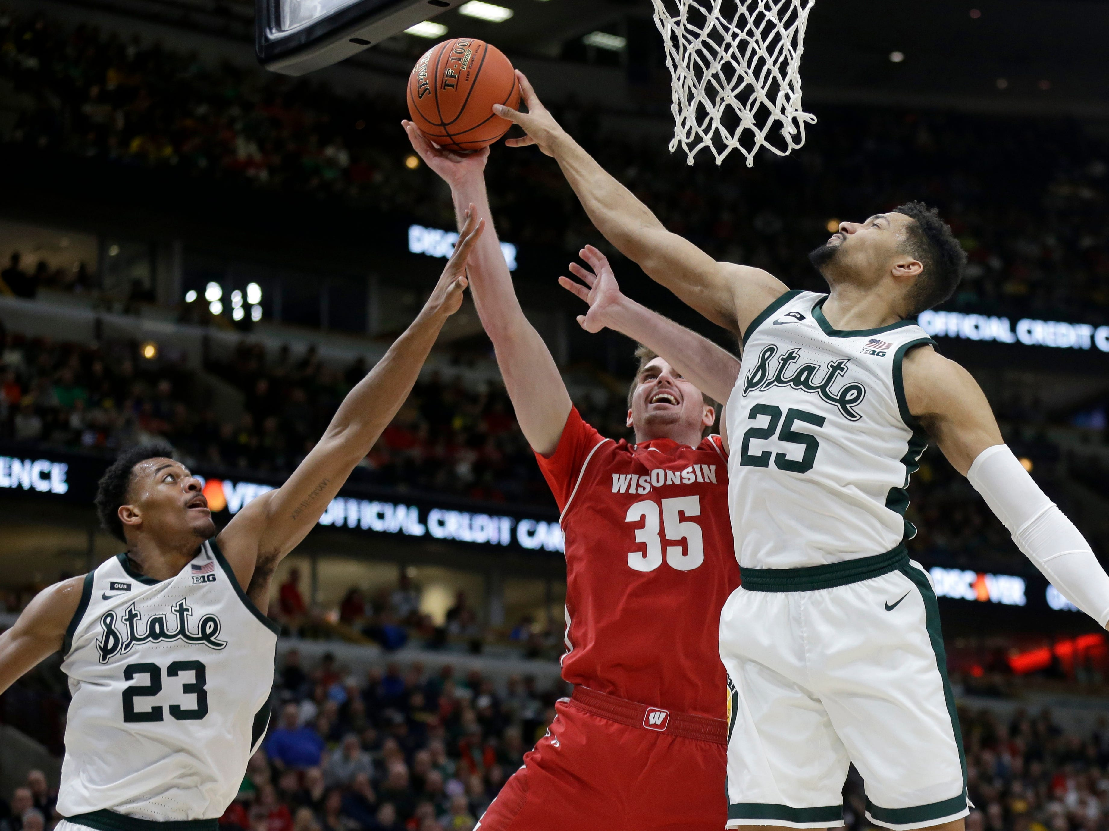 Michigan State's Kenny Goins (25) blocks a shot by Wisconsin's Nate Reuvers (35) during the second half of an NCAA college basketball game in the semifinals of the Big Ten Conference tournament, Saturday, March 16, 2019, in Chicago.