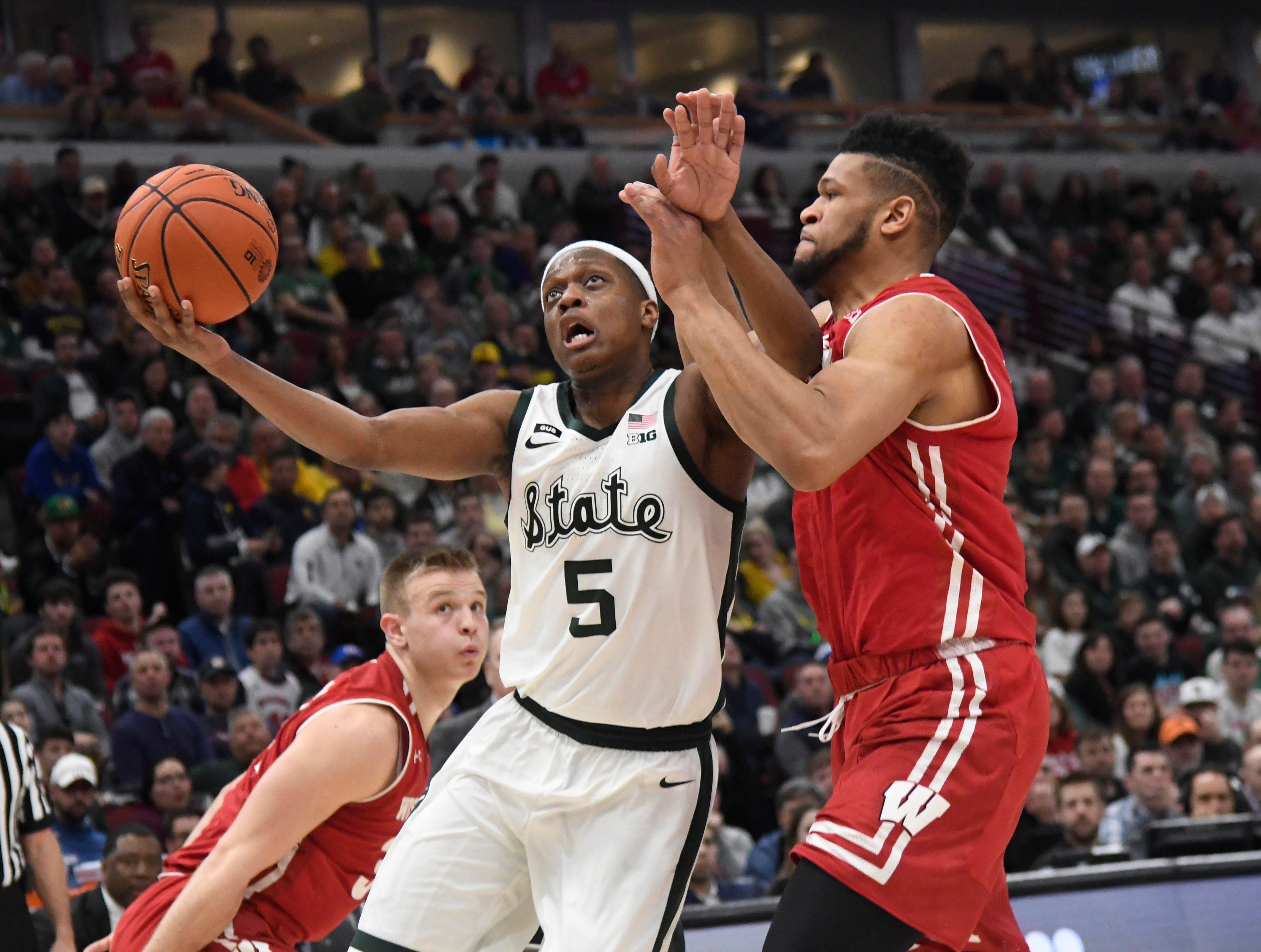 Michigan State Spartans guard Cassius Winston (5) controls the ball as Wisconsin Badgers forward Charles Thomas IV (15) defends during the second half in the Big Ten conference tournament at United Center. Mandatory Credit: David Banks-USA TODAY Sports