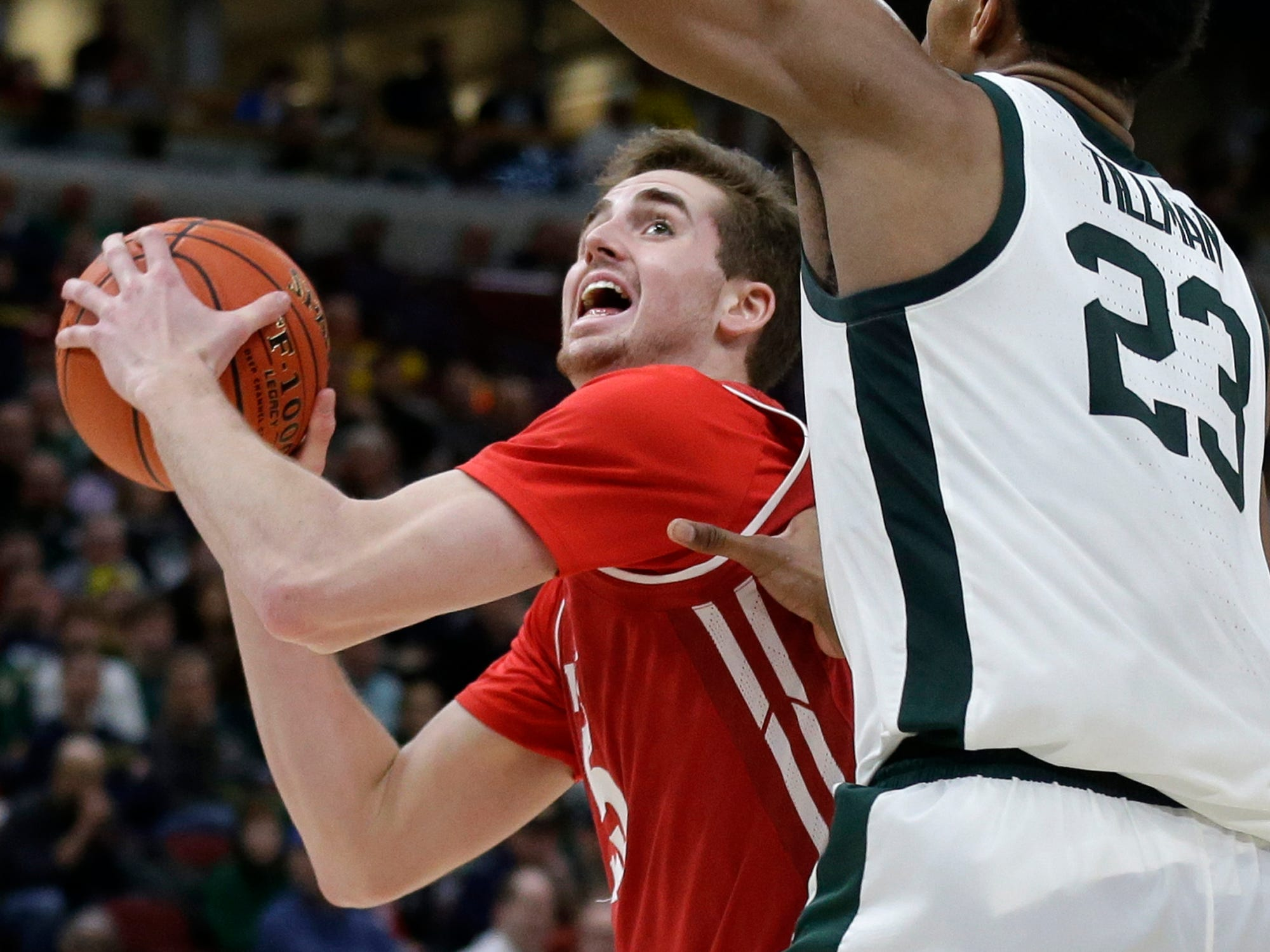 Wisconsin's Nate Reuvers drives against Michigan State's Xavier Tillman (23) during the second half of an NCAA college basketball game in the semifinals of the Big Ten Conference tournament, Saturday, March 16, 2019, in Chicago.