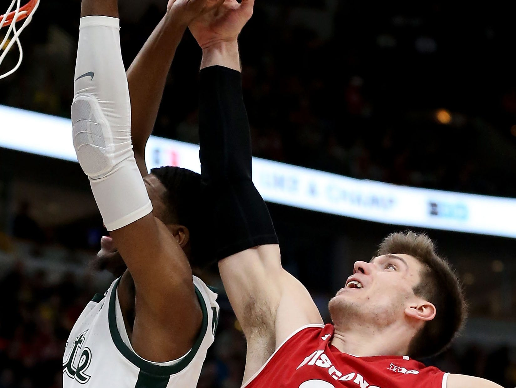 Ethan Happ #22 of the Wisconsin Badgers blocks a shot attempt by Aaron Henry #11 of the Michigan State Spartans in the first half during the semifinals of the Big Ten Basketball Tournament at the United Center on March 16, 2019 in Chicago, Illinois.
