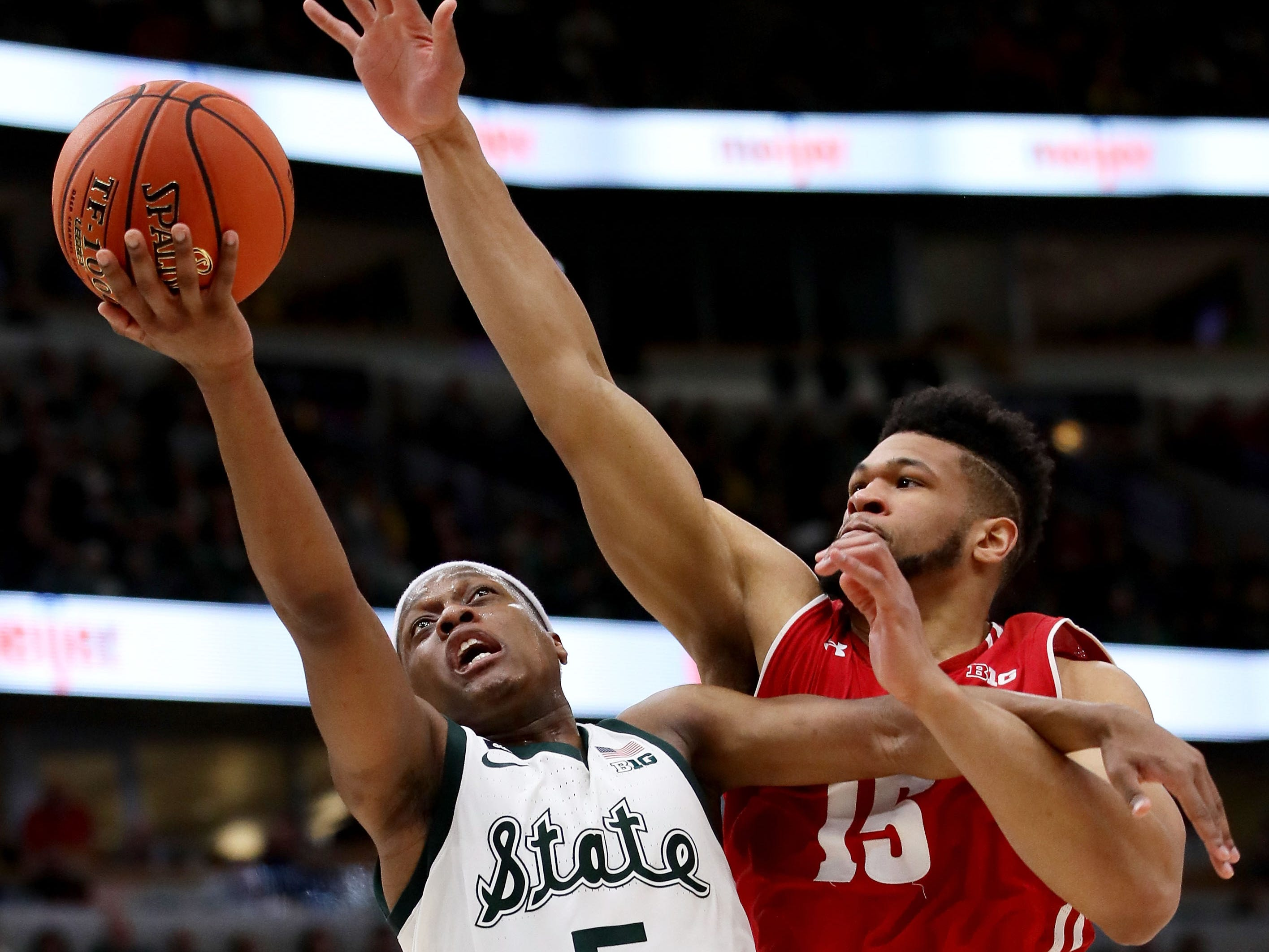 Cassius Winston #5 of the Michigan State Spartans attempts a shot while being guarded by Charles Thomas IV #15 of the Wisconsin Badgers in the second half during the semifinals of the Big Ten Basketball Tournament at the United Center on March 16, 2019 in Chicago, Illinois.