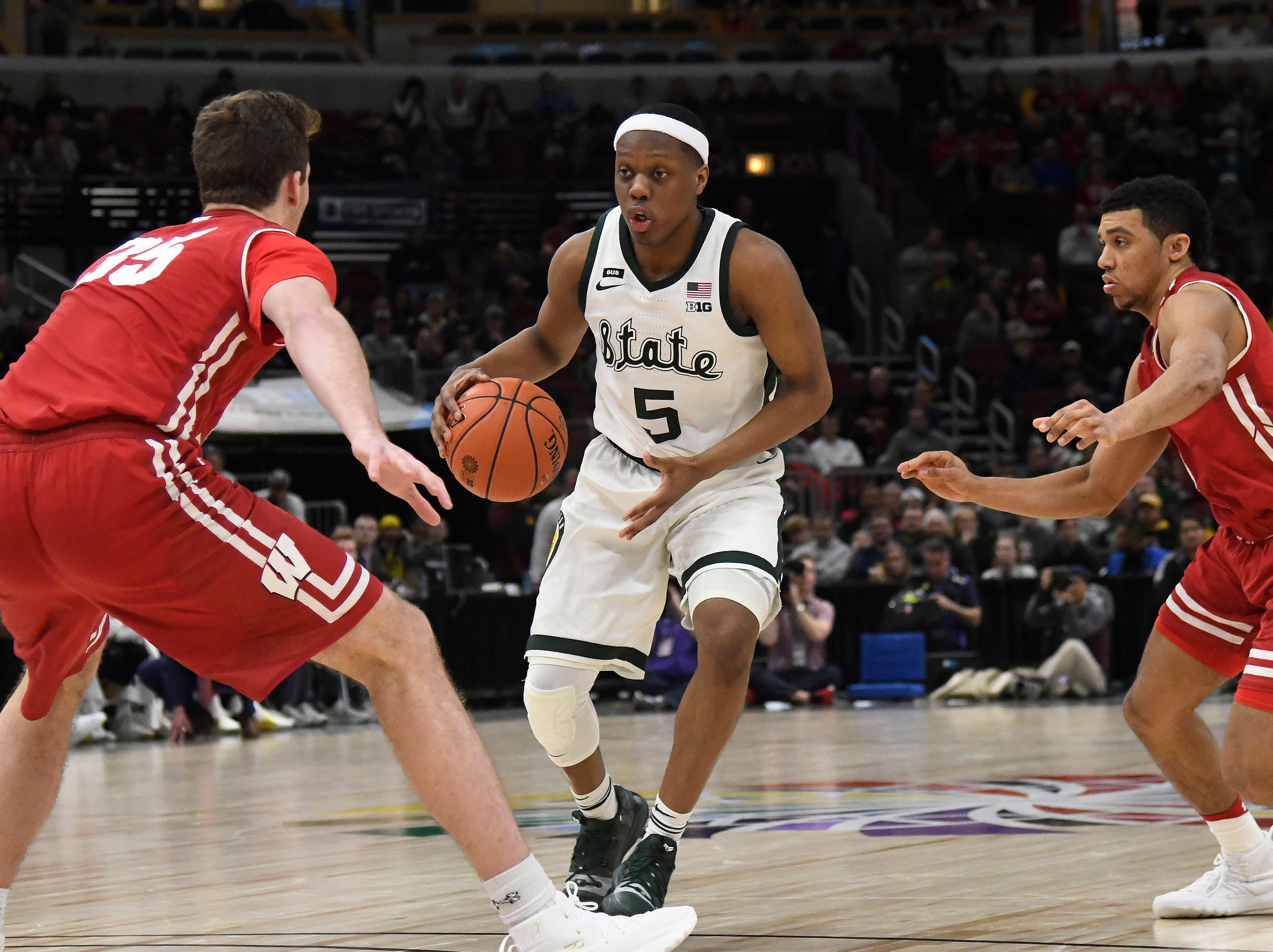 Michigan State Spartans guard Cassius Winston (5) dribbles the ball as Wisconsin Badgers forward Nate Reuvers (35) and guard Khalil Iverson (21) defend during the second half in the Big Ten conference tournament at United Center.