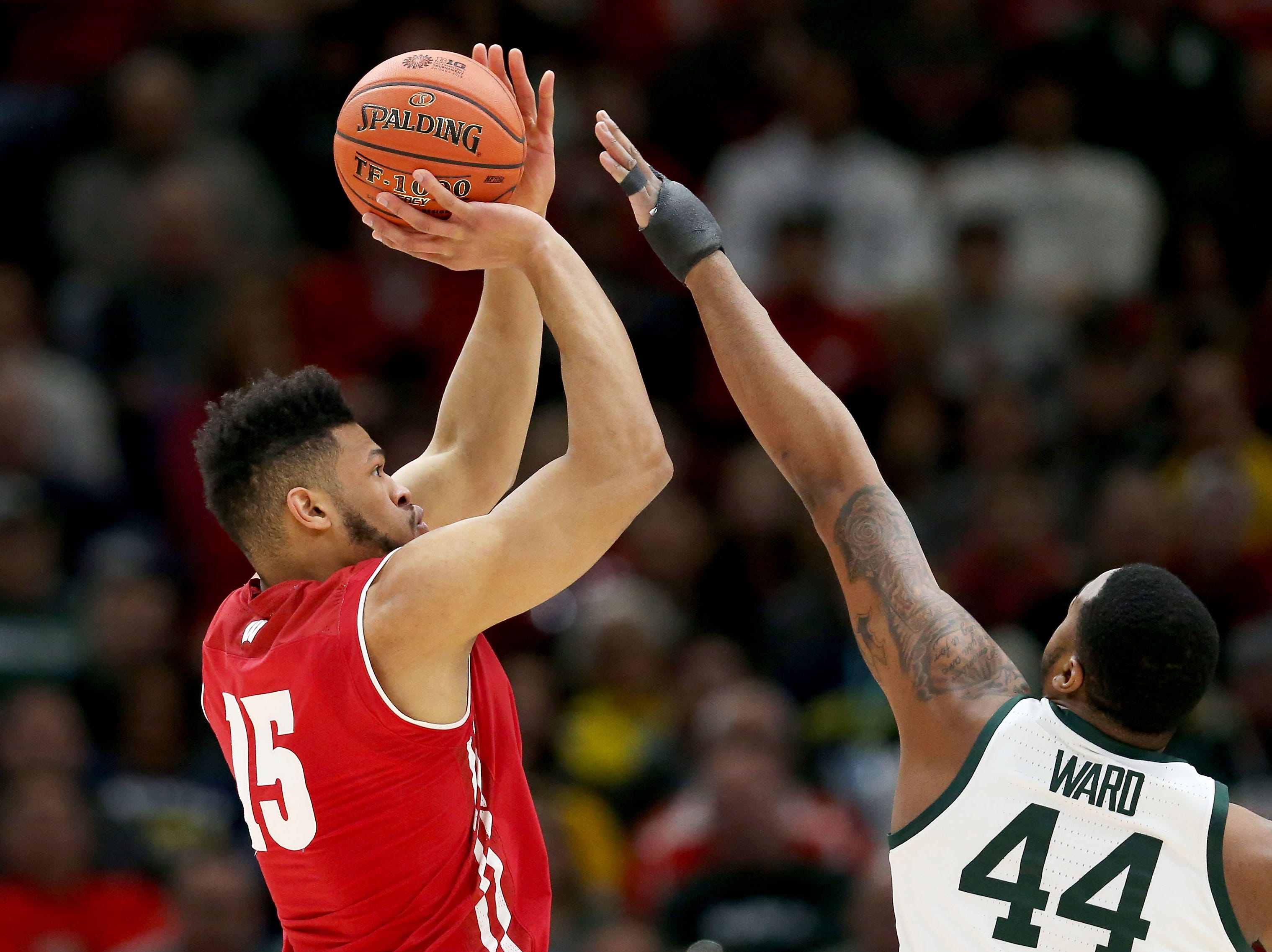 Charles Thomas IV #15 of the Wisconsin Badgers attempts a shot while being guarded by Nick Ward #44 of the Michigan State Spartans in the first half during the semifinals of the Big Ten Basketball Tournament at the United Center on March 16, 2019 in Chicago, Illinois.