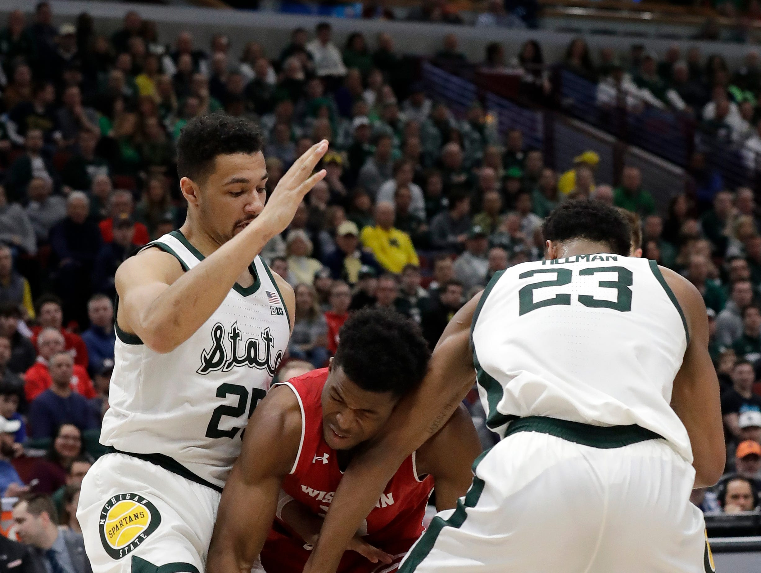 Wisconsin's Khalil Iverson goes after a loose ball against Michigan State's Kenny Goins (25) and Xavier Tillman (23) during the first half of an NCAA college basketball game in the semifinals of the Big Ten Conference tournament, Saturday, March 16, 2019, in Chicago.