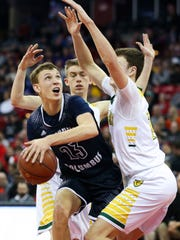 Columbus Catholic's Bryce Fuerlinger (23) maneuvers for a shot in the lane against Sheboygan Lutheran in the WIAA Division 5 boys basketball state championship game Saturday at the Kohl Center in Madison.