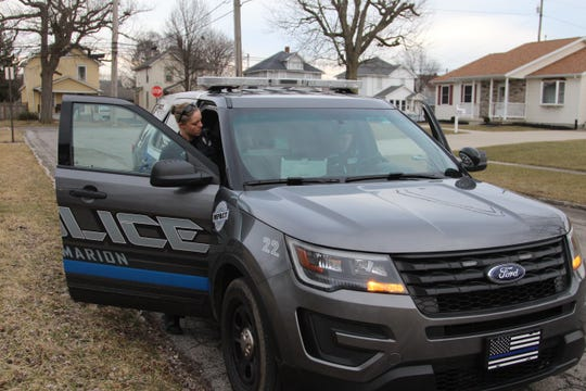 Officer Erica Tetreault, with the Marion Police Department, gets into her police cruiser parked on Congress Street after responding to a domestic dispute. Officer Kaitlyn Meadows sits in the driver's seat.