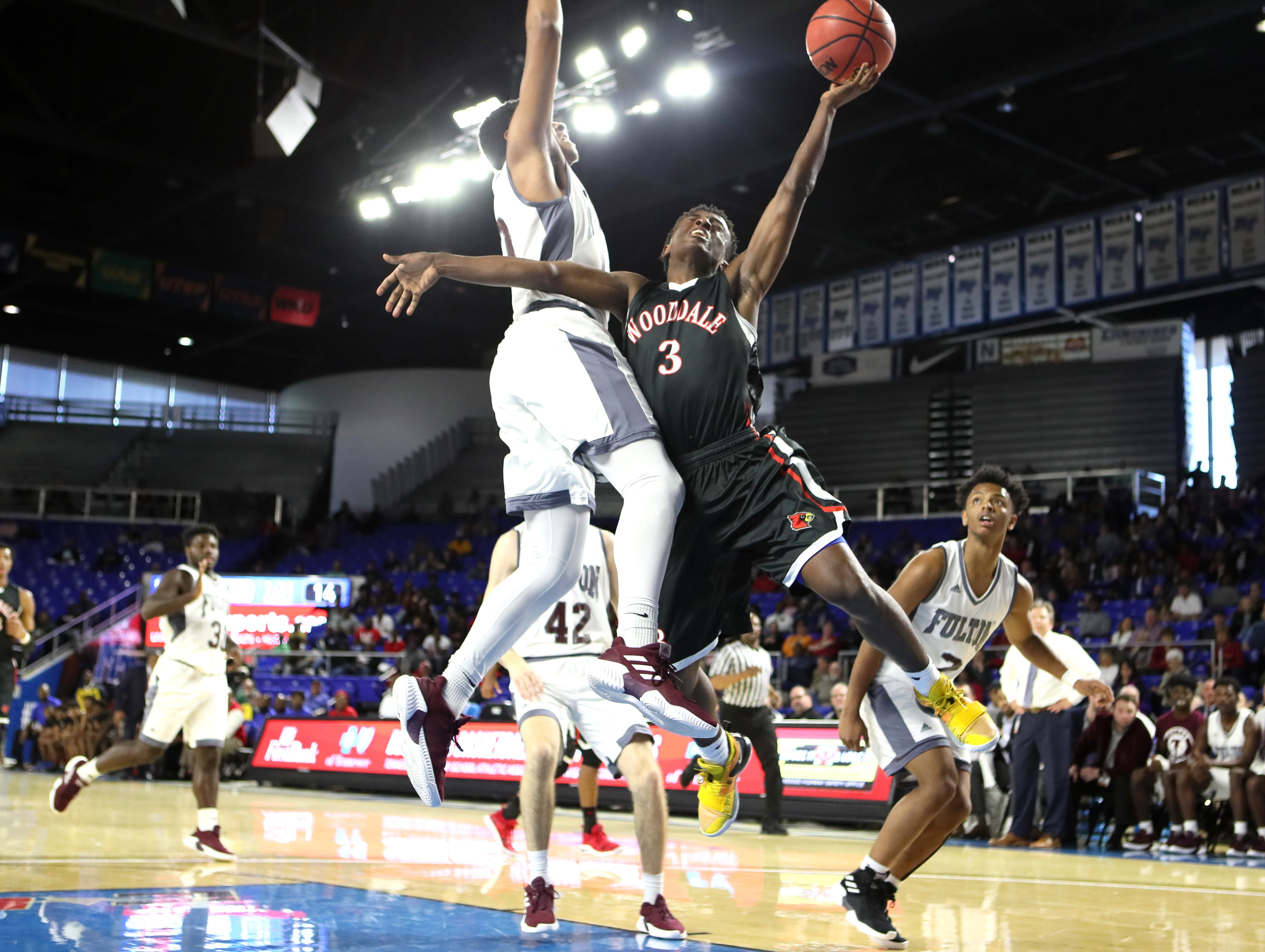Wooddale's Alvin Miles is fouled on a shot attempt by Fulton's Trey West during the Class AA boys basketball state championship game at the Murphy Center in Murfreesboro, Tenn. on Saturday, March 16, 2019.