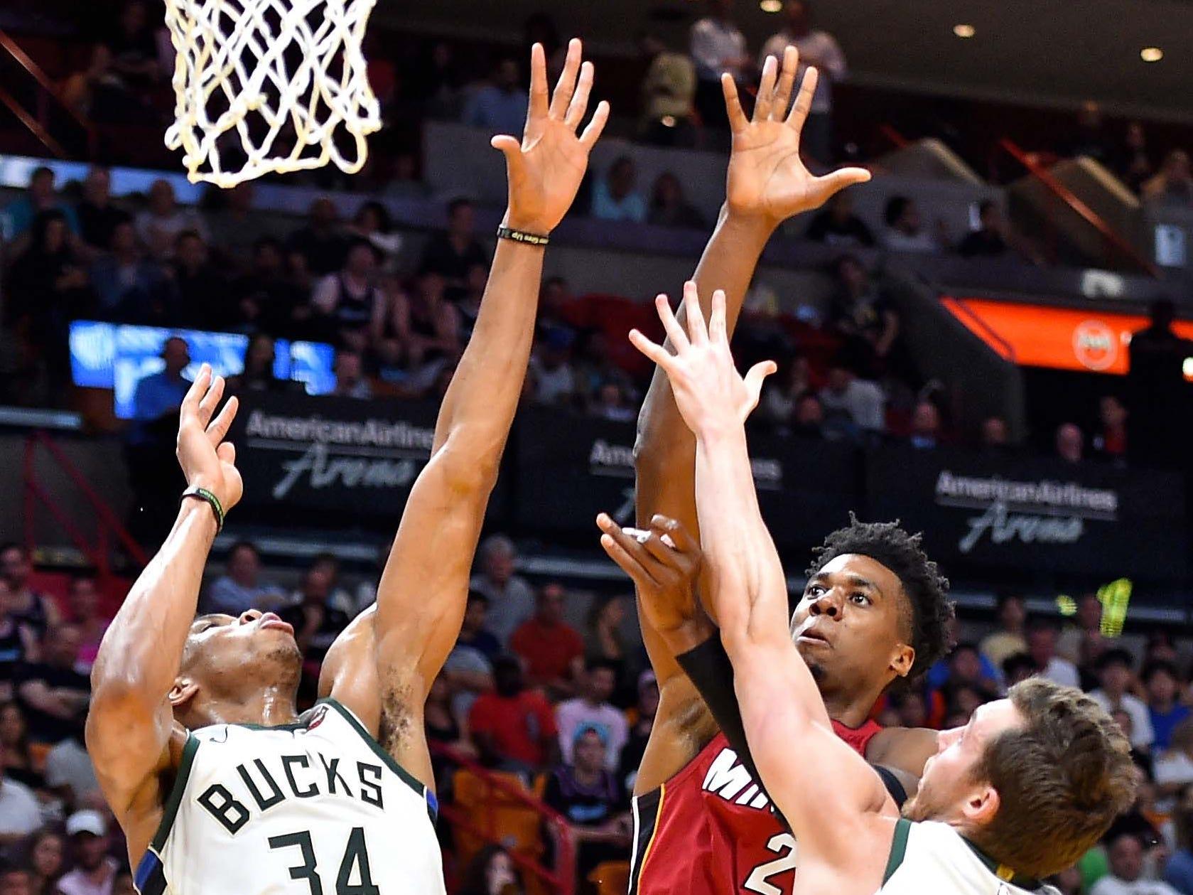 Heat center Hassan Whiteside (21) shoots between Bucks forward Giannis Antetokounmpo and Bucks guard Pat Connaughton.