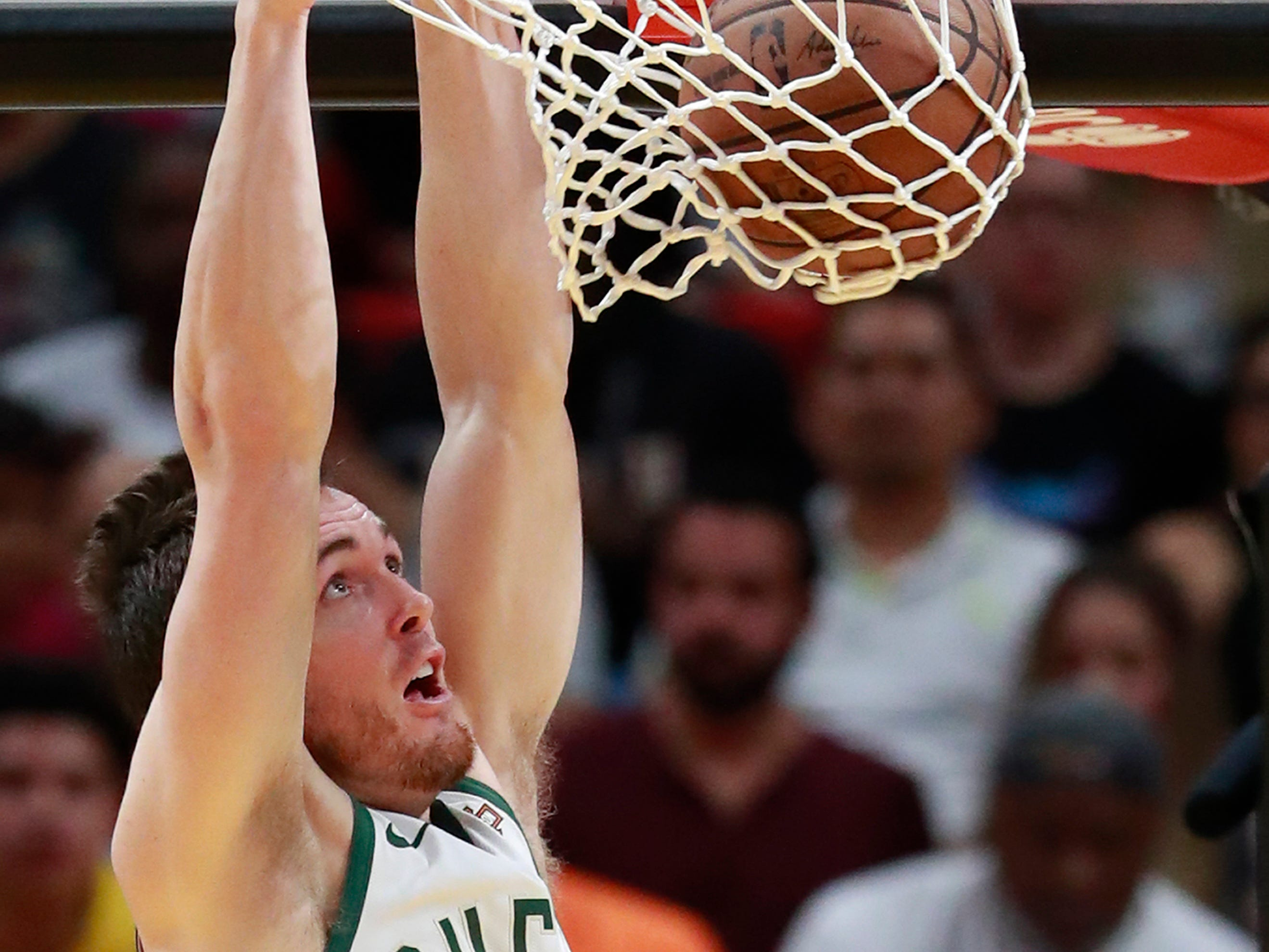 Bucks guard Pat Connaughton finishes a dunk and hangs on the rim.