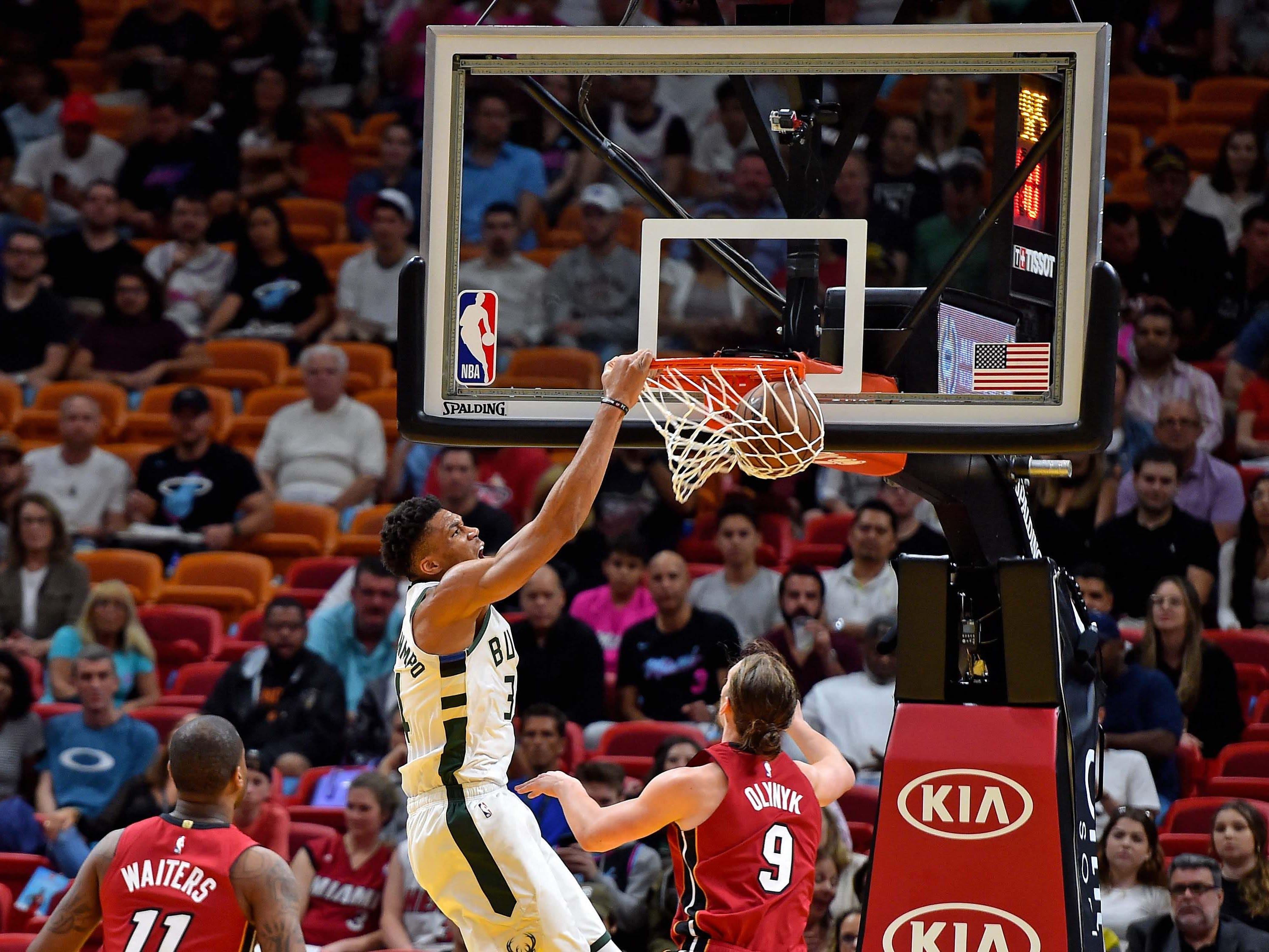 Bucks forward Giannis Antetokounmpo dunks in front of Miami Heat forward Kelly Olynyk.