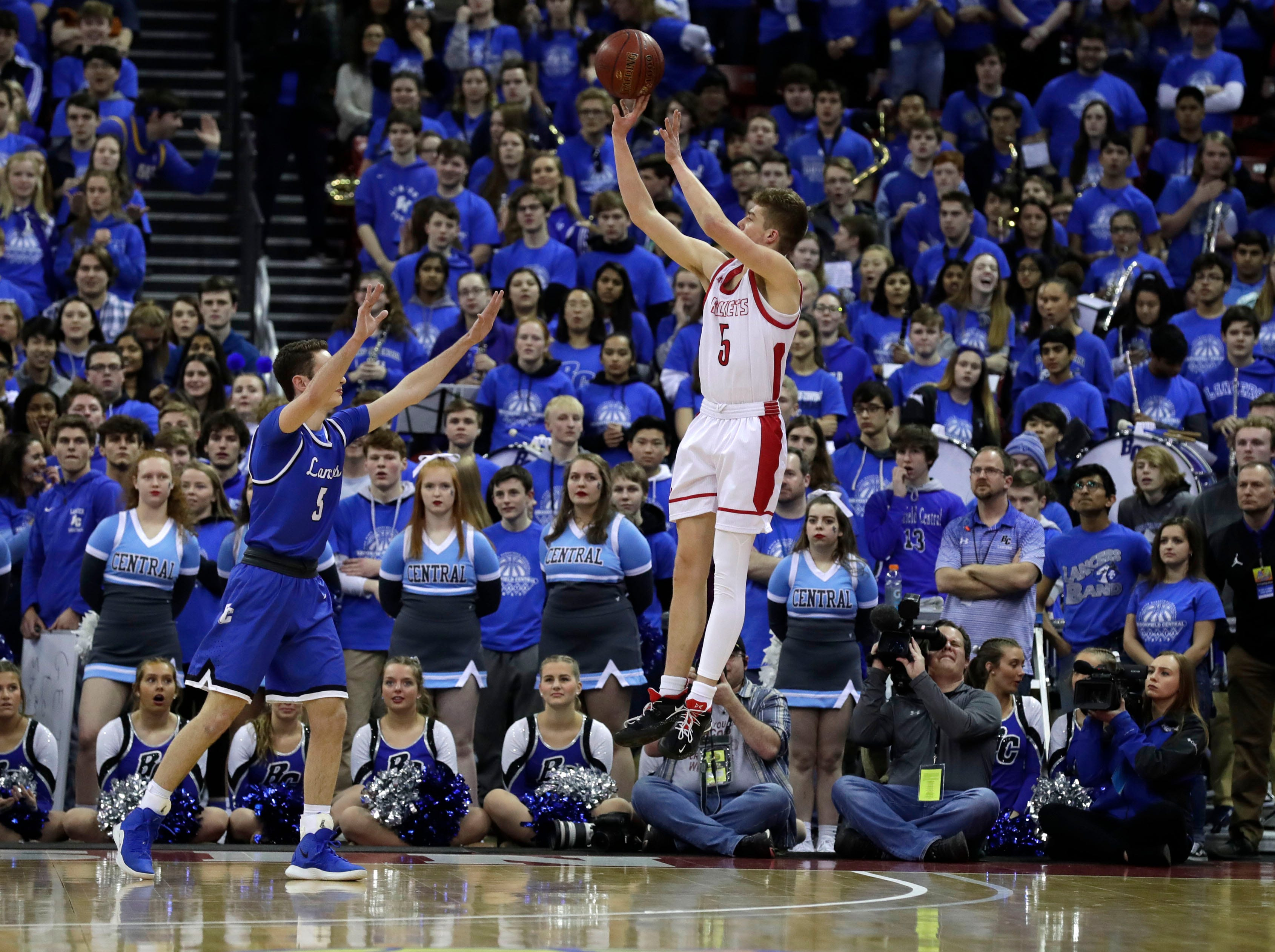 Neenah's Max Klesmit hits a shot Friday night with the Brookfield Central student section watching.