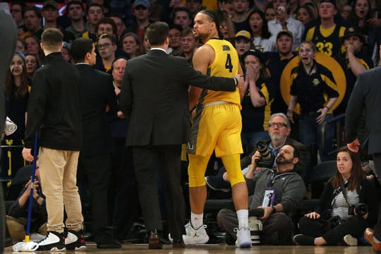Marquette forward Theo John is escorted from the court after being ejected, just one part of the craziness Friday night during the Golden Eagles' loss to Seton Hall.