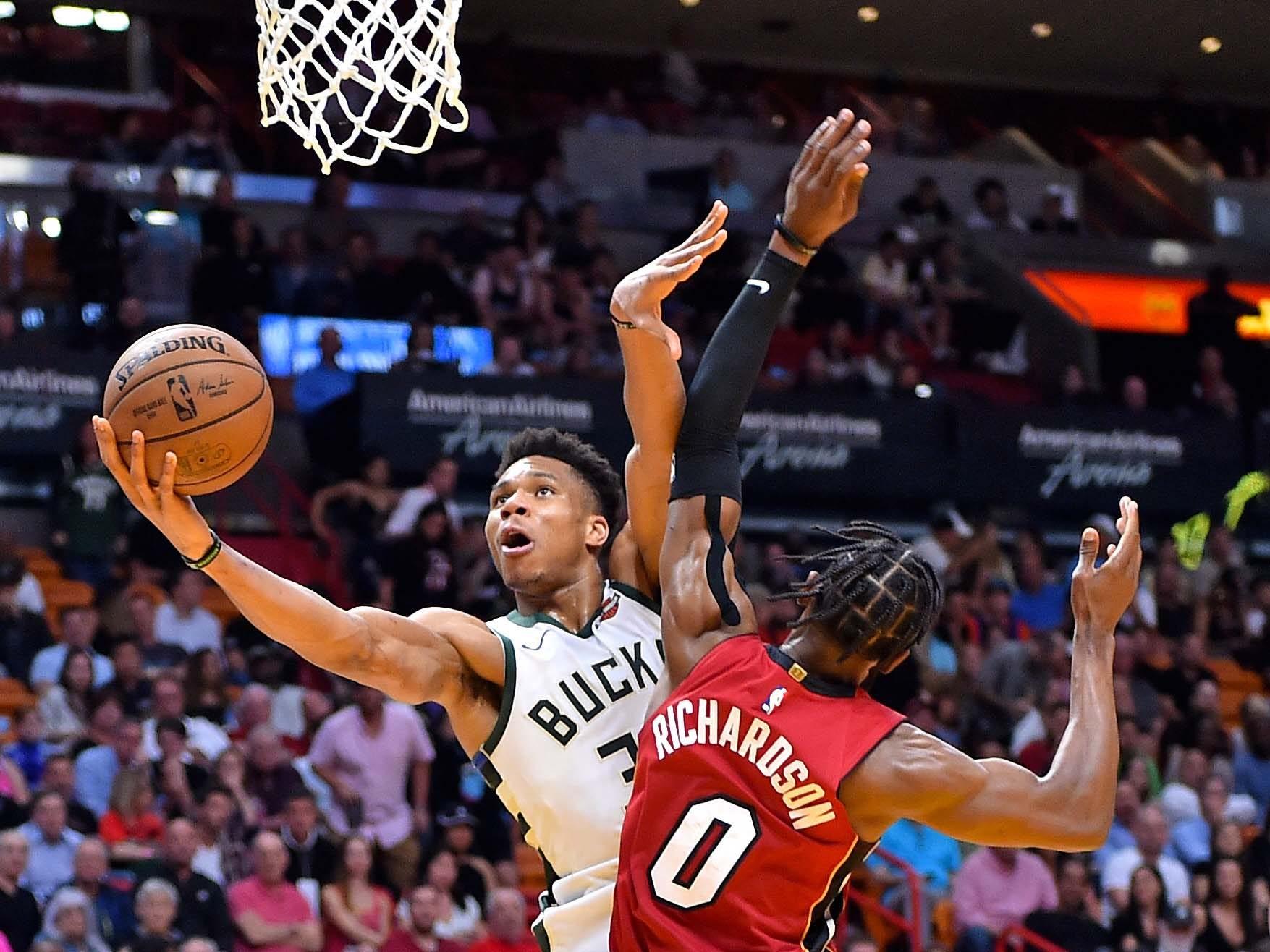 Bucks forward Giannis Antetokounmpo is fouled by Heat guard Josh Richardson.
