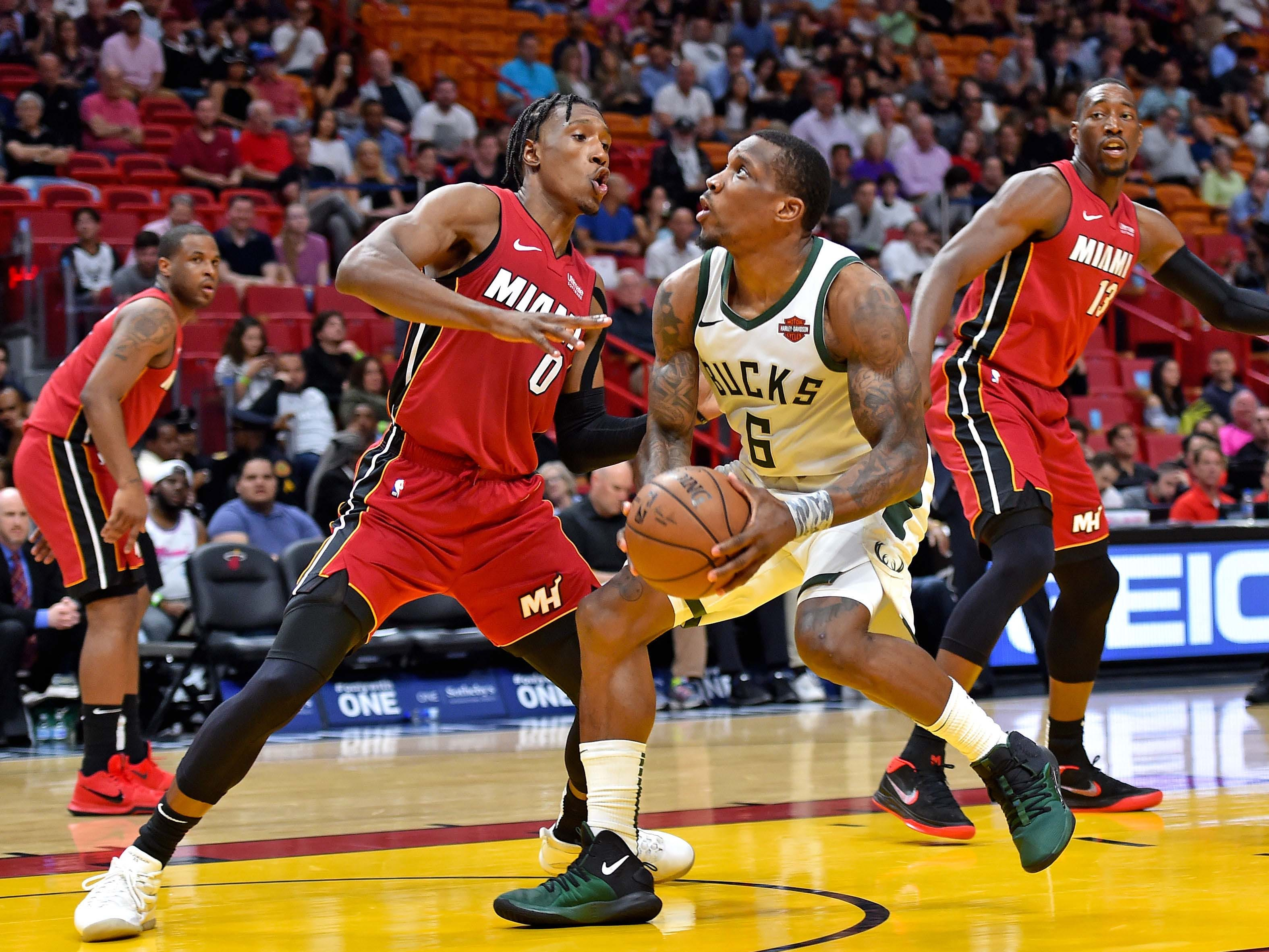 Bucks guard Eric Bledsoe attacks the basket despite the defense of Miami's Josh Richardson.