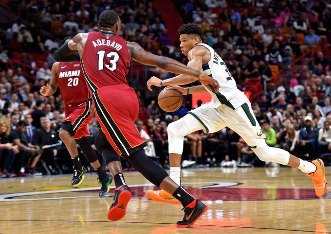 Heat center Bam Adebayo tries to cut off Giannis Antetokounmpo on his way toward the the basket.